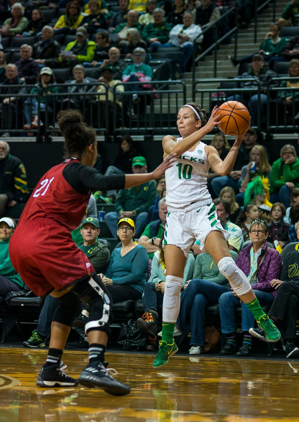 Oregon Ducks Lexi Bando (#10) keeps the ball away from Southern Utah's defender. The University of Oregon Ducks women basketball team defeated the Southern Utah Thunderbirds 98-38 in Matthew Knight Arena Saturday afternoon. The Ducks had four players in double-digits: Ruthy Hebard with 13; Mallory McGwire with 10; Lexi Bando with 17 which included four three-pointers; and Sabrina Ionescu with 16 points. The Ducks overwhelmed the Thunderbirds, shooting 50% in field goals to South Utah's 26.8%, 53.8% in three-pointers to 12.5%, and 85.7% in free throws to 50%. The Ducks, with an overall record of 8-1, and coming into this game ranked 9th, will play their next home game against Ole Miss on December 17. Photo by Rhianna Gelhart, Oregon News Lab