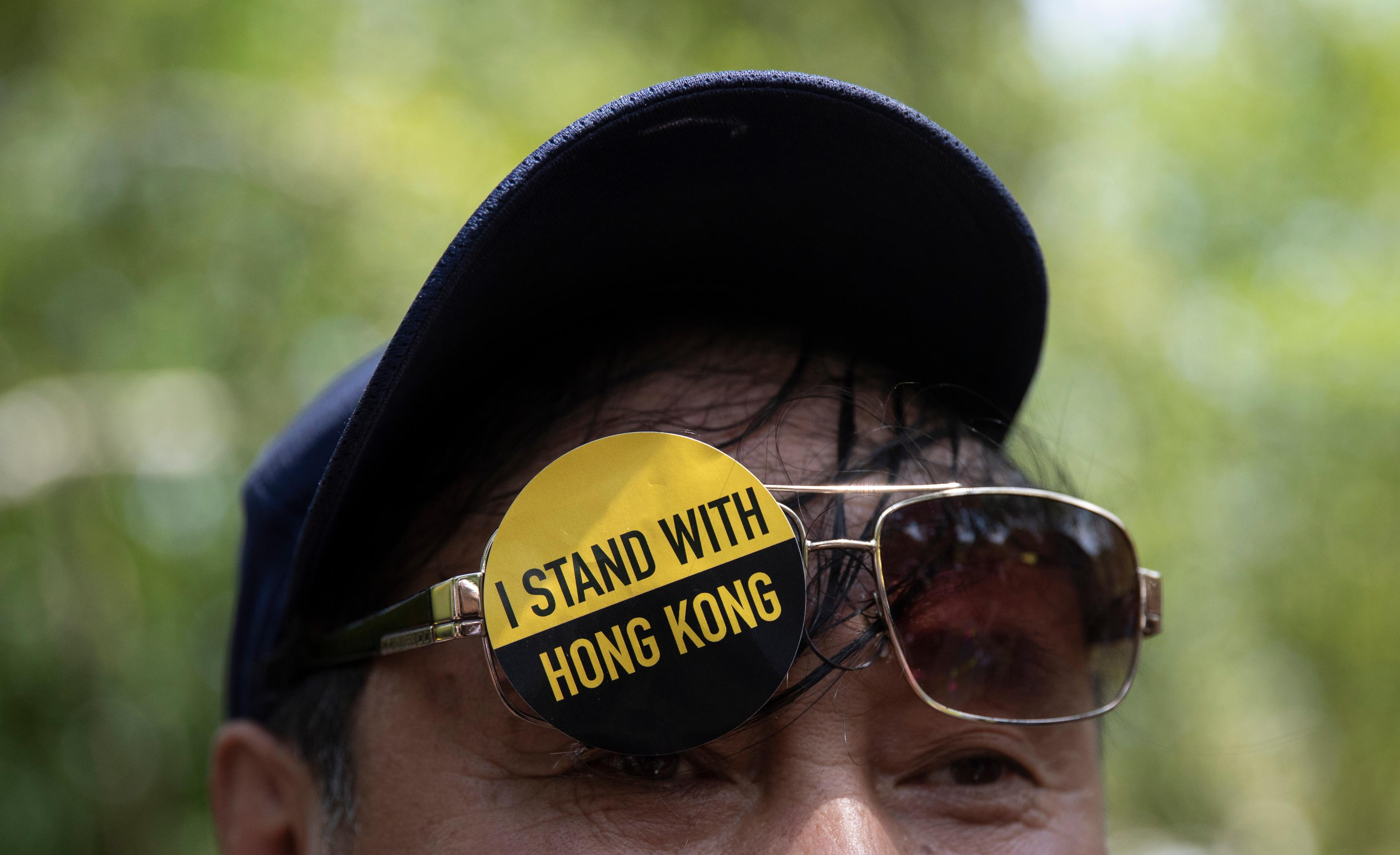 "A man with a sticker that reads ""I Stand With Hong Kong"" on his glasses gathered with others in Lafayette Square in front of the White House in Washington, Sunday, Aug. 18, 2019, in solidarity with the ""Stand With Hong Kong, Power to the People Rally"" in Hong Kong. (AP Photo/Carolyn Kaster)"