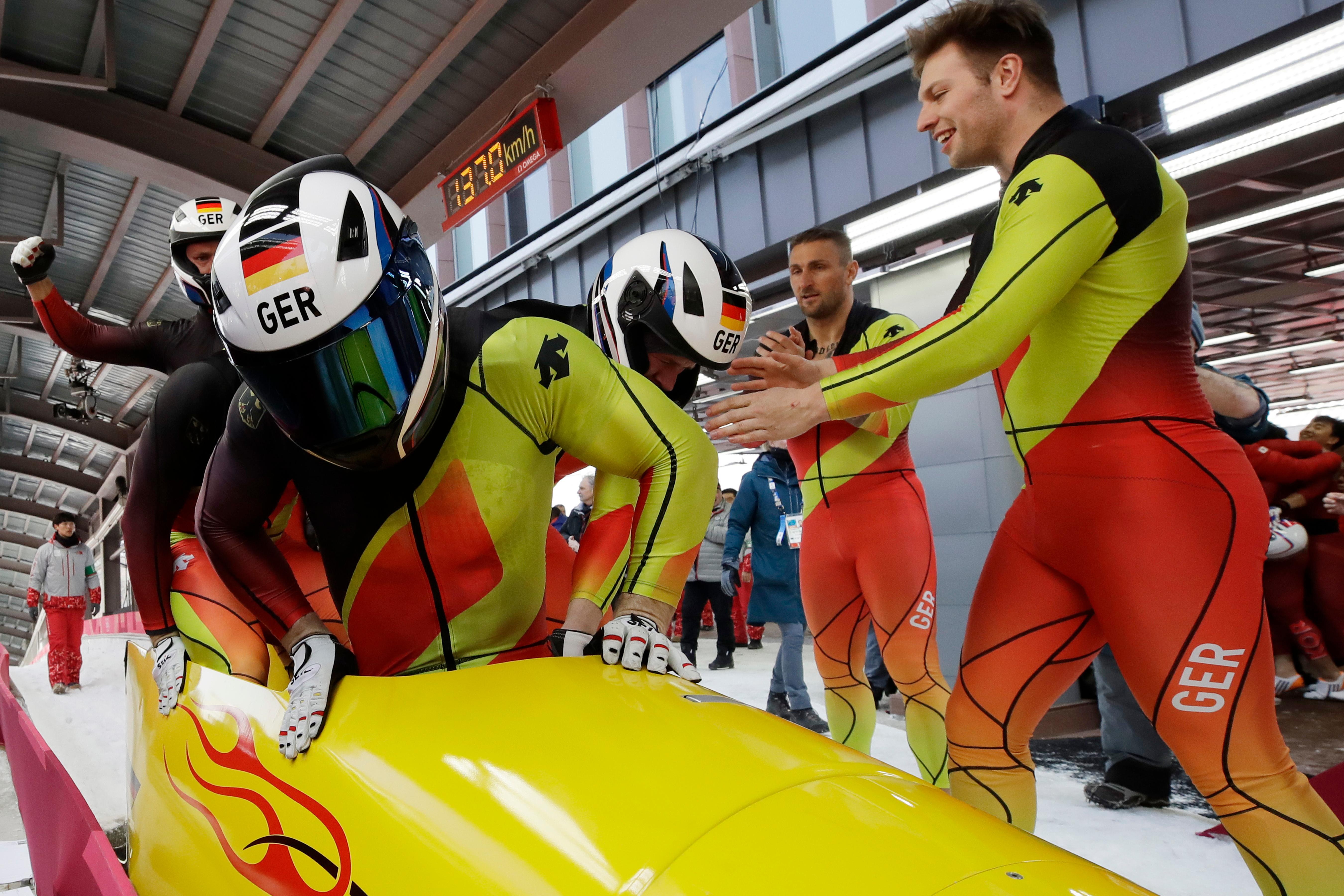 Driver Francesco Friedrich, Candy Bauer, Martin Grothkopp and Thorsten Margis of Germany celebrate after winning the gold at the four-man bobsled competition final at the 2018 Winter Olympics in Pyeongchang, South Korea, Sunday, Feb. 25, 2018. (AP Photo/Andy Wong)