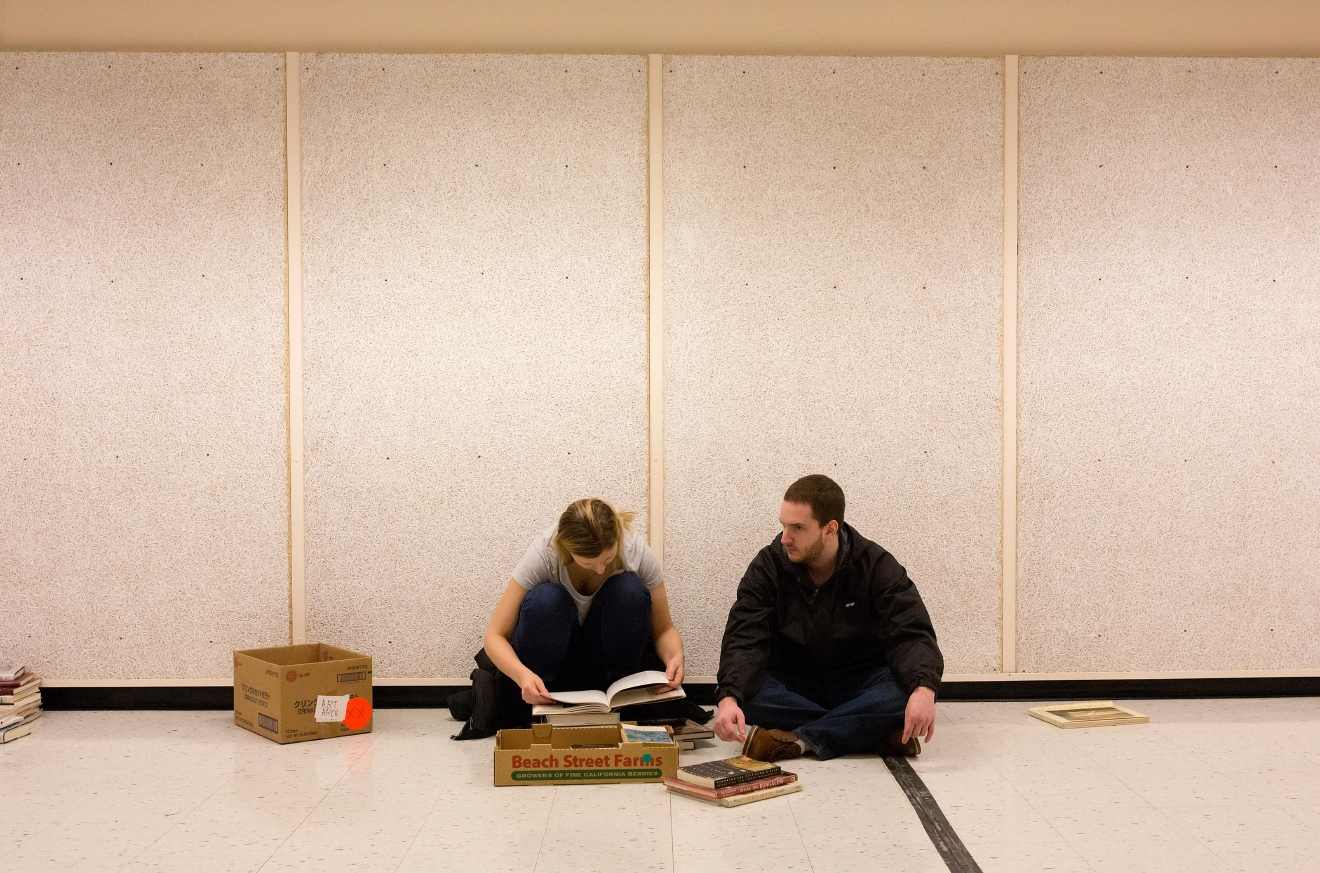 Engaged couple Matt Wilhelmsen and Carliana Halterman sort through their fiction and architecture books to see what they will be bringing home at the Big Book Sale 2017 at the Seattle Center Exhibition Hall. (Sy Bean / Seattle Refined)