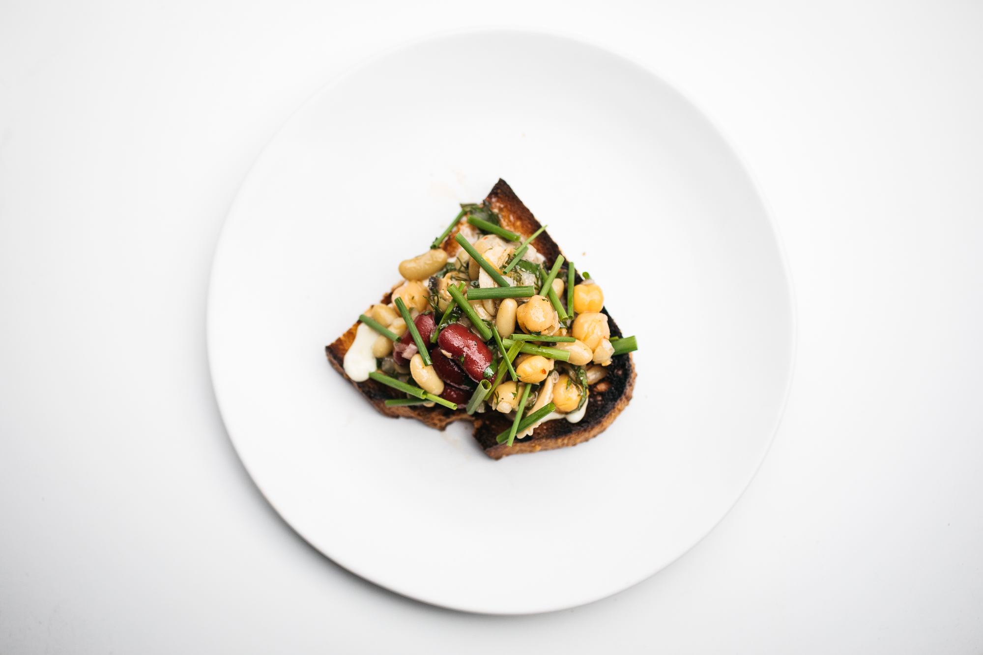 Course 2: Marinated mixed beans salad with middleneck clams, spring herbs, guanicale, and lemon on sourdough toast (Image: Betty Clicker Photography)