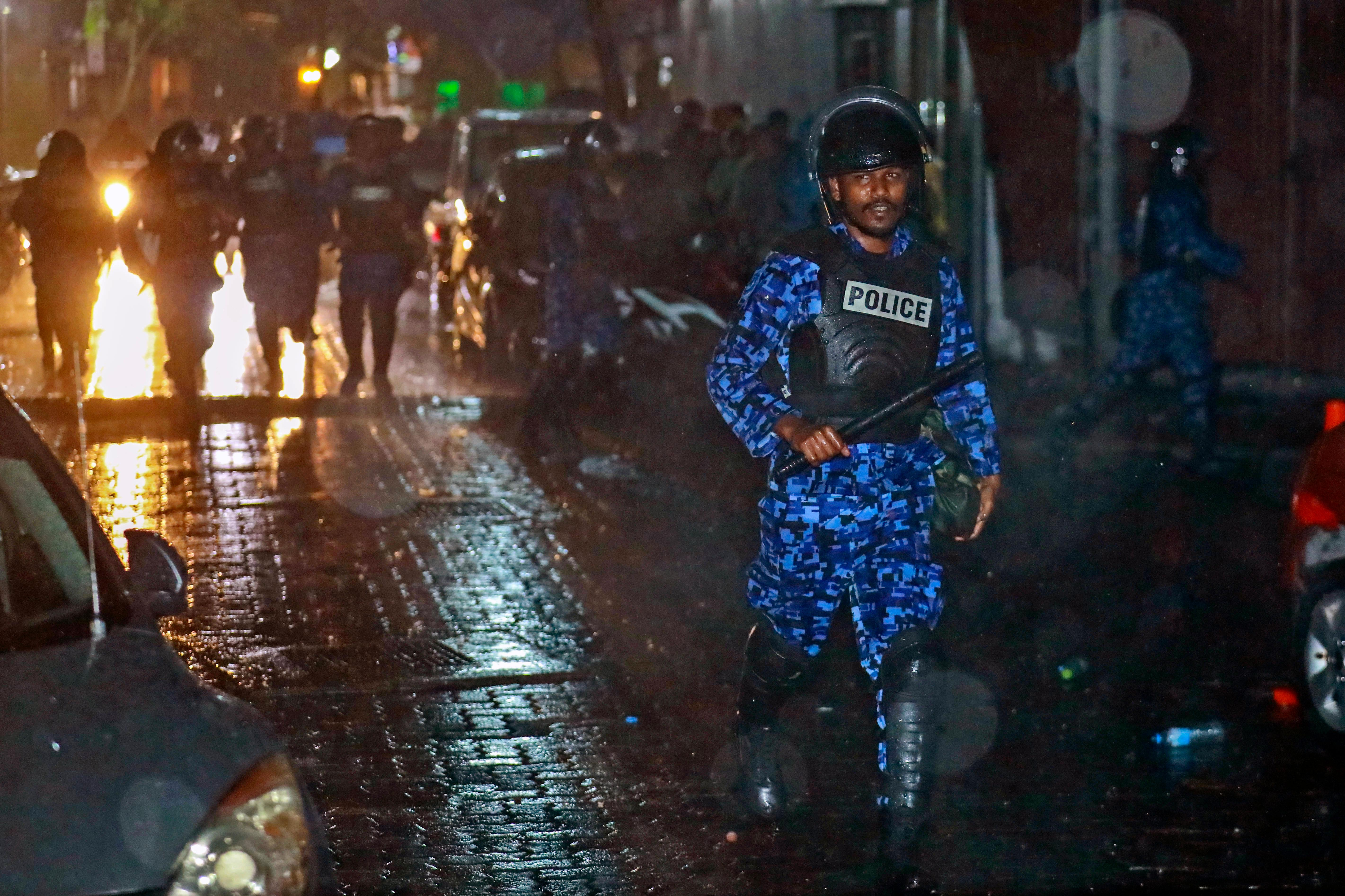 A Maldives policeman charges with baton towards protesters after the government declared a 15-day state of emergency in Male, Maldives, early Tuesday, Feb. 6, 2018. The Maldives government declared a 15-day state of emergency Monday as the political crisis deepened in the Indian Ocean nation amid an increasingly bitter standoff between the president and the Supreme Court. Hours after the emergency was declared, soldiers forced their way into the Supreme Court building, where the judges were believed to be taking shelter, said Ahmed Maloof, an opposition member of Parliament. (AP Photo/Mohamed Sharuhaan)