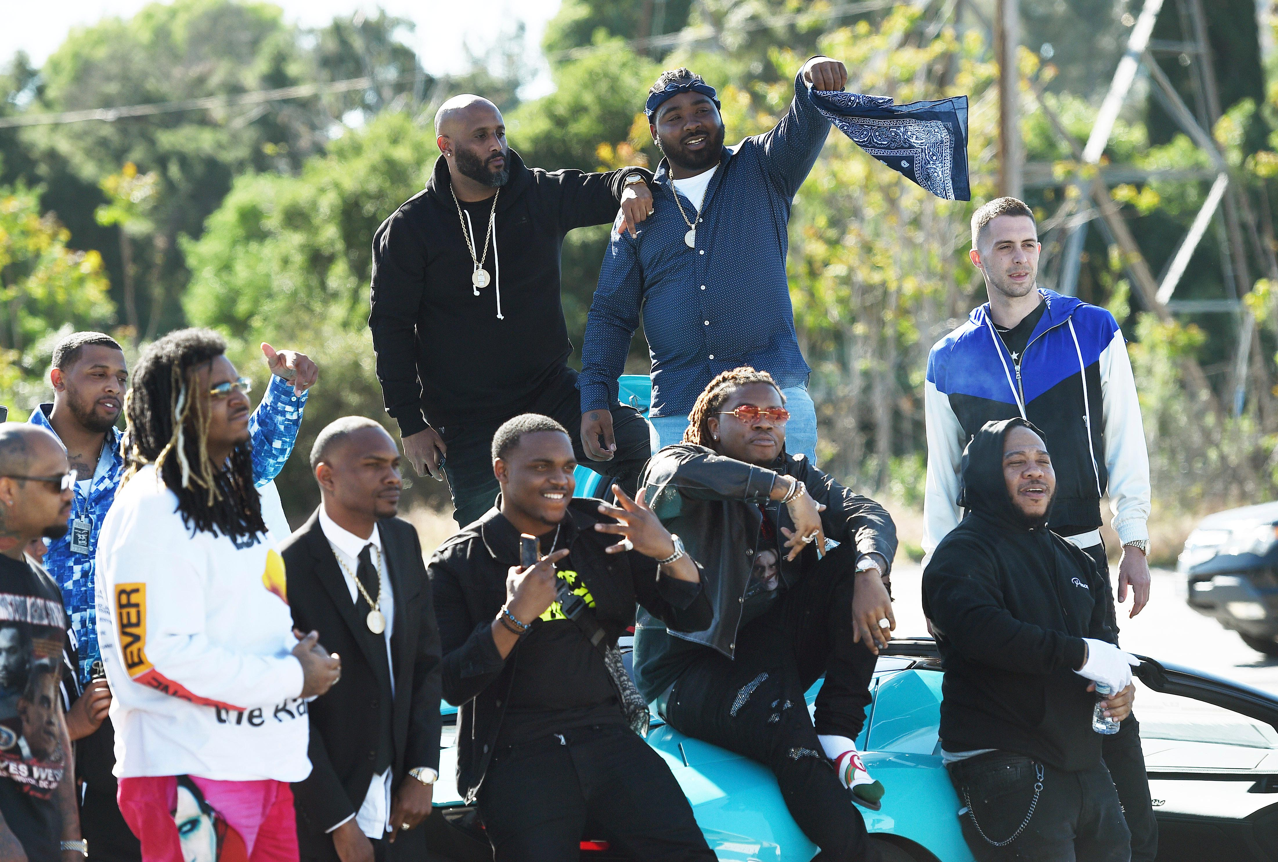 Attendees of a burial service for the late rapper Nipsey Hussle stage to tribute to him before they leave the Forest Lawn Hollywood Hills cemetery, Friday, April 12, 2019 in Los Angeles. (Photo by Chris Pizzello/Invision/AP)