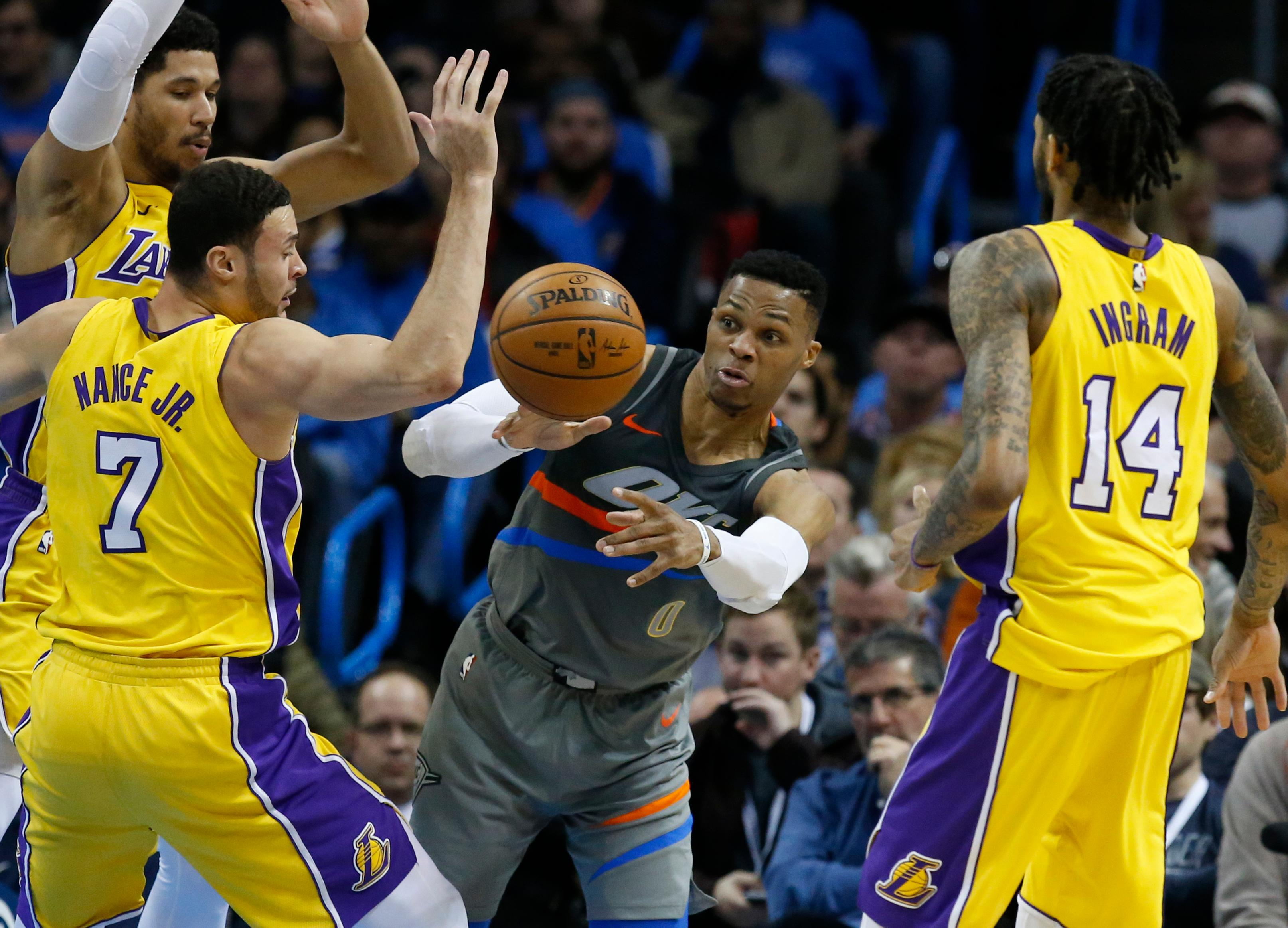 Oklahoma City Thunder guard Russell Westbrook (0) passes between Los Angeles Lakers forwards Larry Nance Jr. (7) and Brandon Ingram (14) in the first half of an NBA basketball game in Oklahoma City, Sunday, Feb. 4, 2018. (AP Photo/Sue Ogrocki)