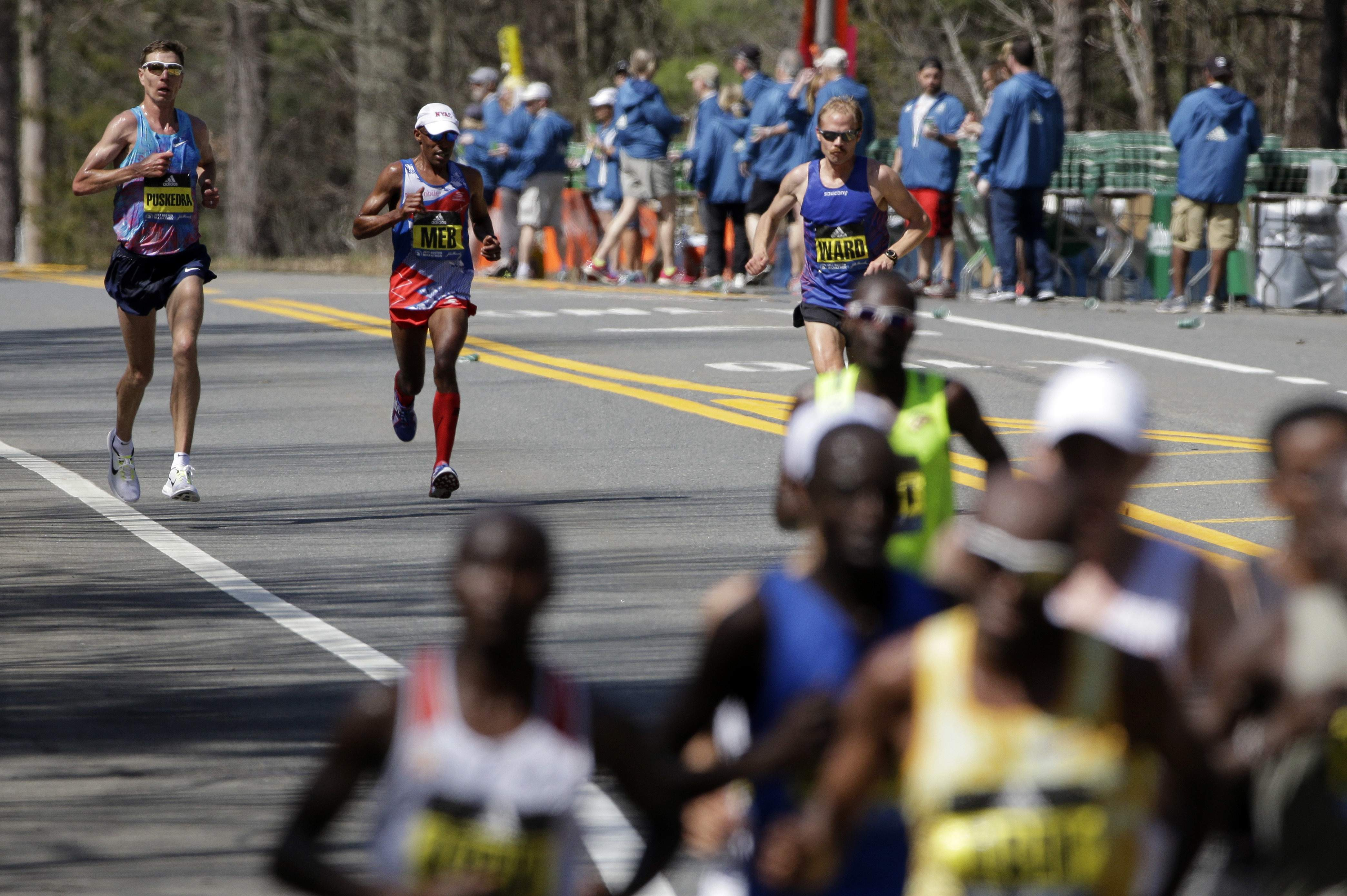 Luke Puskedra, left, Meb Keflezighi and Jared Ward, all of the United States, run behind the leaders in the 121st Boston Marathon on Monday, April 17, 2017, in Natick, Mass. THE ASSOCIATED PRESS