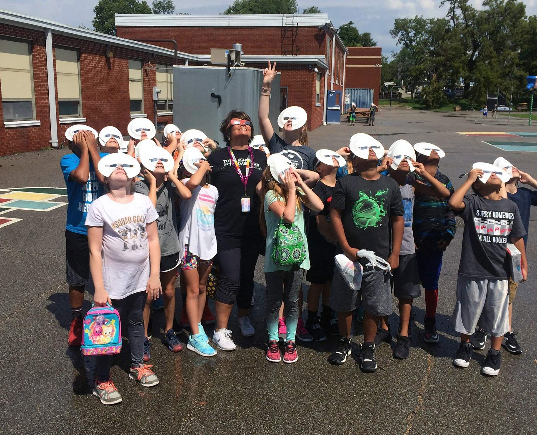 Principal Monica Shane and students and Blue Hills Elementary enjoying the start of the eclipse. [Photo courtesy of Fort Osage School District]