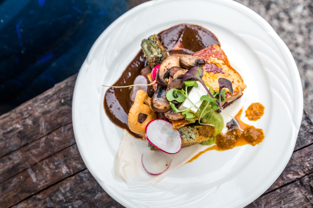 Mole Negro: pork belly, panela, micro flowers, crema, salsa, bean puree, corn cake, queso fresco, radishes, chicharron chip, and cilantro flowers / Image: Catherine Viox // Published: 6.18.19