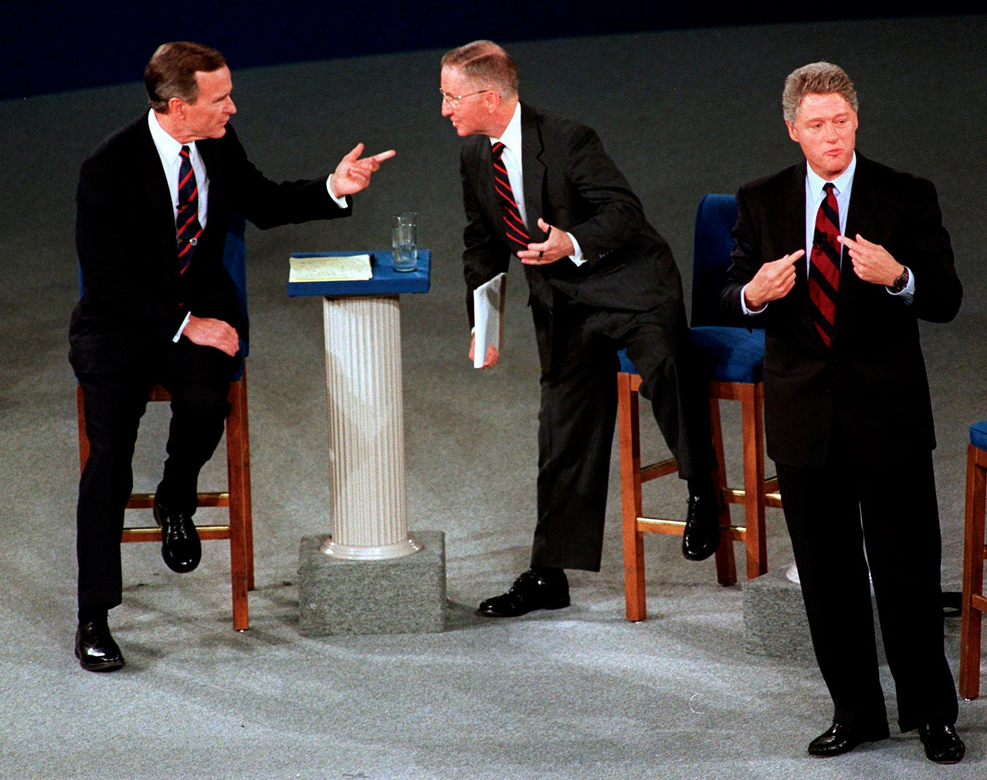 FILE - In this Oct. 15, 1992, file photo, President George H.W. Bush, left, talks with independent candidate Ross Perot as Democratic candidate Bill Clinton stands aside at the end of their second presidential debate in Richmond, Va. Bush died at the age of 94 on Friday, Nov. 30, 2018, about eight months after the death of his wife, Barbara Bush. (AP Photo/Marcy Nighswander, File)