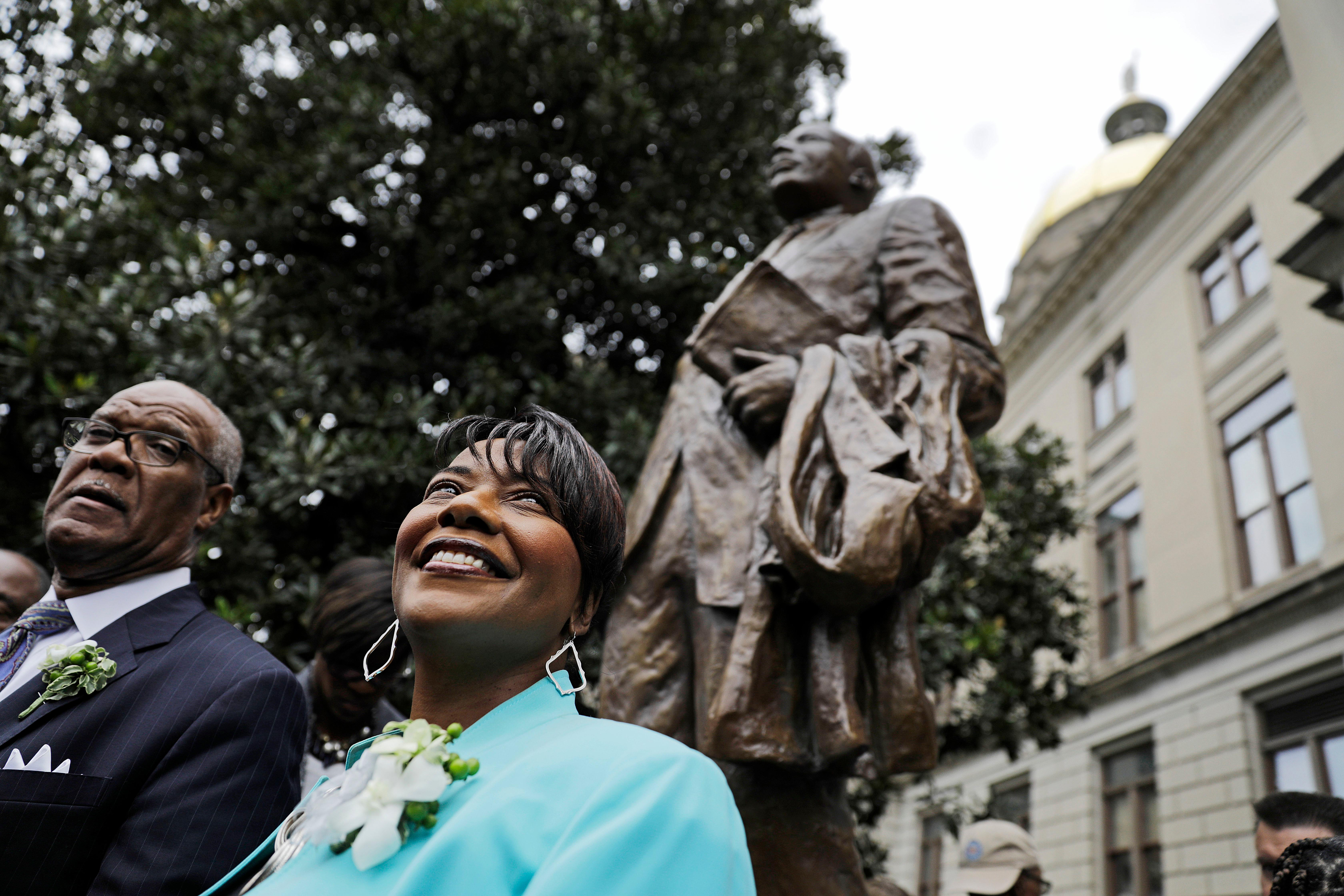 "The Rev. Bernice King, right, daughter of the Rev. Martin Luther King Jr., stands under a statue paying tribute to her father, after it's unveiled on the state Capitol grounds in Atlanta, Monday, Aug. 28, 2017. The statue's unveiling Monday came more than three years after Georgia lawmakers endorsed the project. A replica of the nation's Liberty Bell tolled three times before the 8-foot (2.44-meter) bronze statue was unveiled on the 54th anniversary of King's ""I have a dream"" speech at the march on Washington. (AP Photo/David Goldman)"