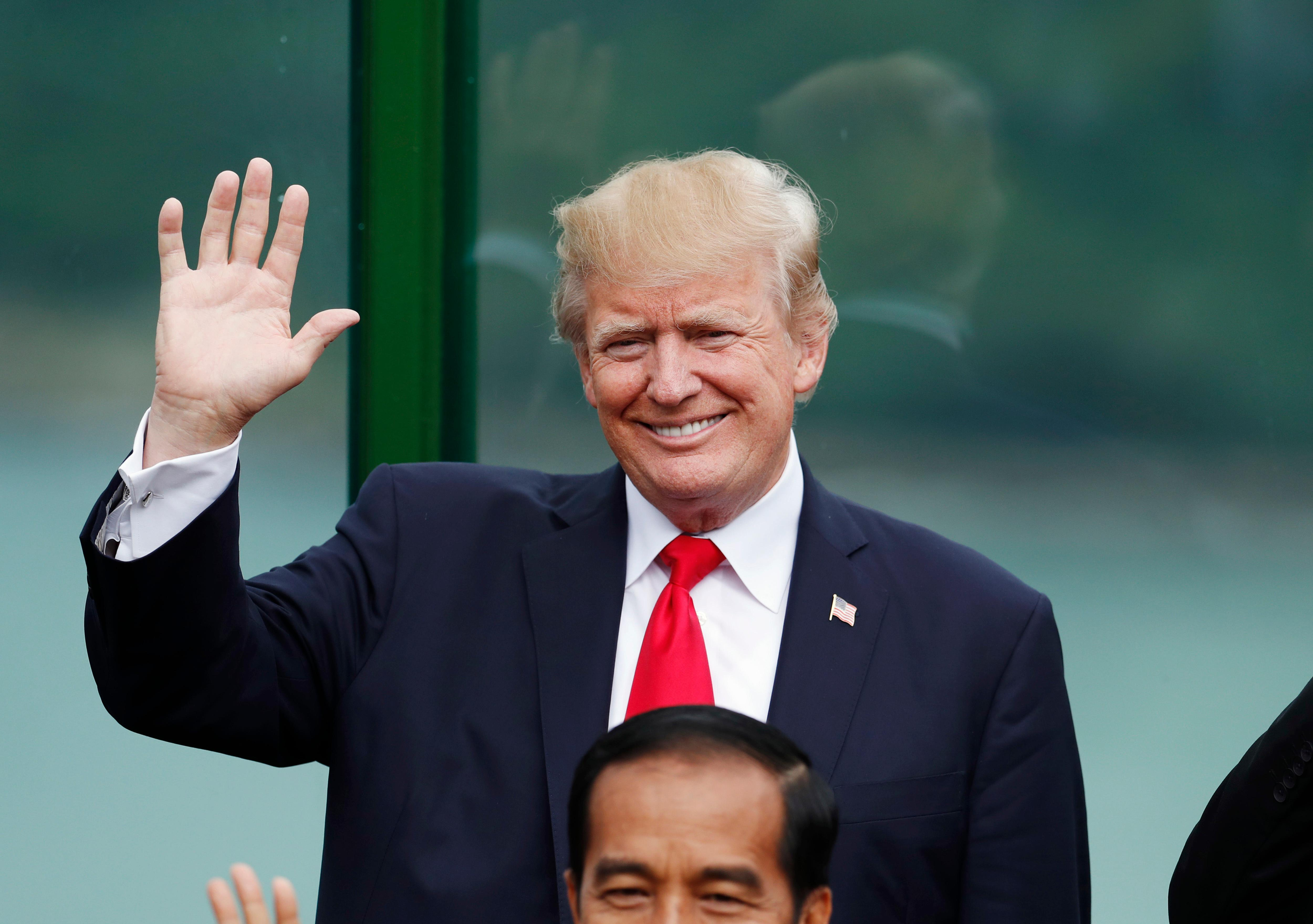 U.S. President Donald Trump holds up his hand during the family photo session at the APEC Summit in Danang, Vietnam, Saturday, Nov. 11, 2017. (Jorge Silva/Pool Photo via AP)
