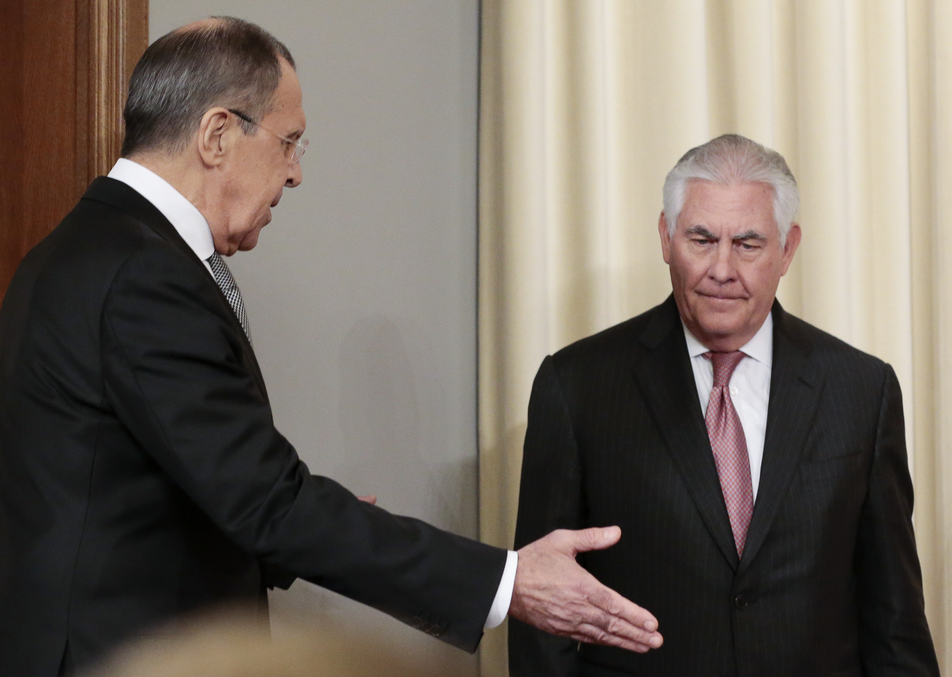 Russian Foreign Minister Sergey Lavrov, left, welcomes US Secretary of State Rex Tillerson to attend a news conference following their talks in Moscow, Russia, Wednesday, April 12, 2017. Amid a fierce dispute over Syria, the United States and Russia agreed Wednesday to work together on an international investigation of a Syrian chemical weapons attack last week. (AP Photo/Ivan Sekretarev)