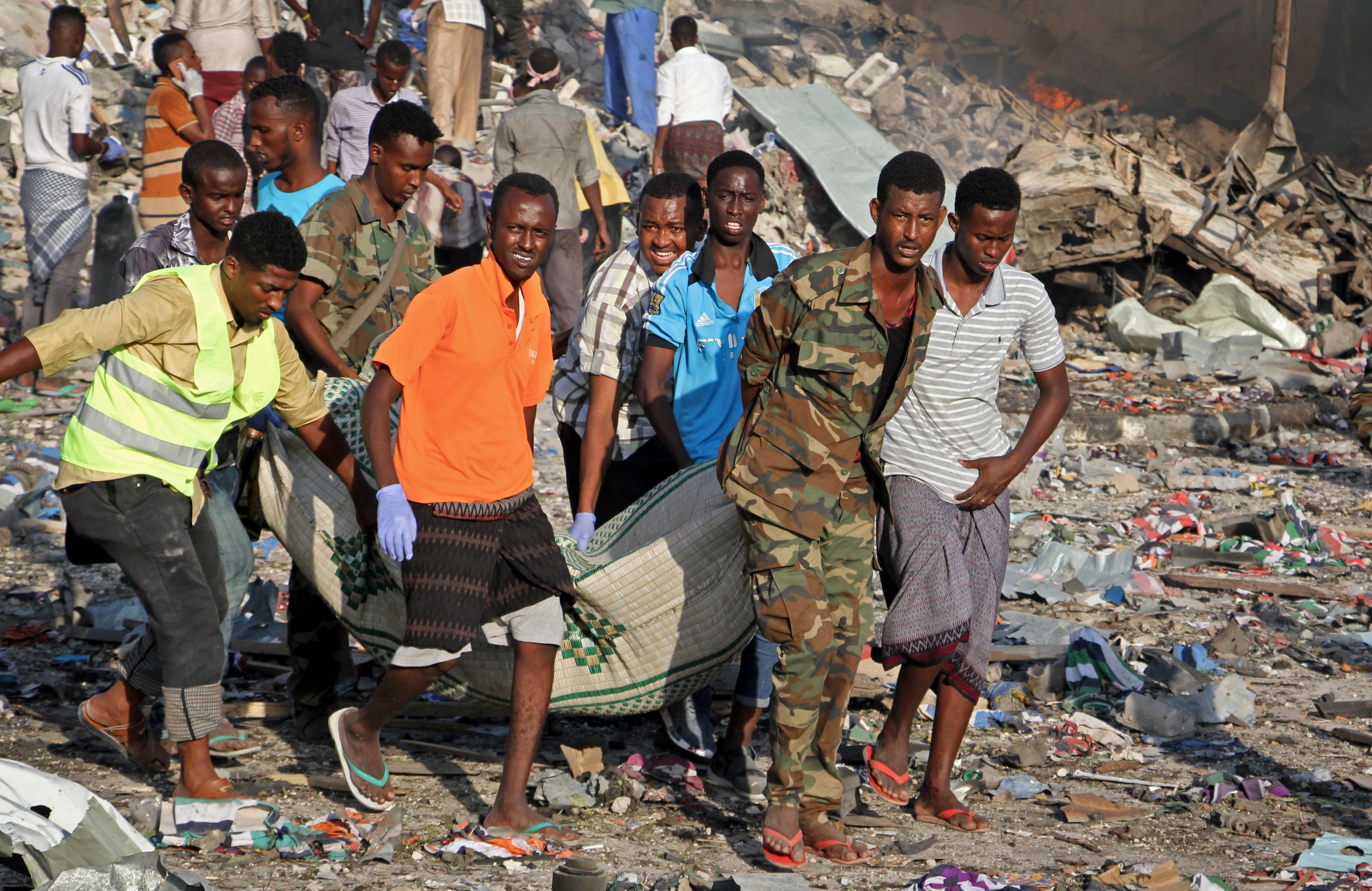 Somalis remove the body of a man killed in a blast in the capital Mogadishu, Somalia Saturday, Oct. 14, 2017. A huge explosion from a truck bomb has killed at least 20 people in Somalia's capital, police said Saturday, as shaken residents called it the most powerful blast they'd heard in years. (AP Photo/Farah Abdi Warsameh)