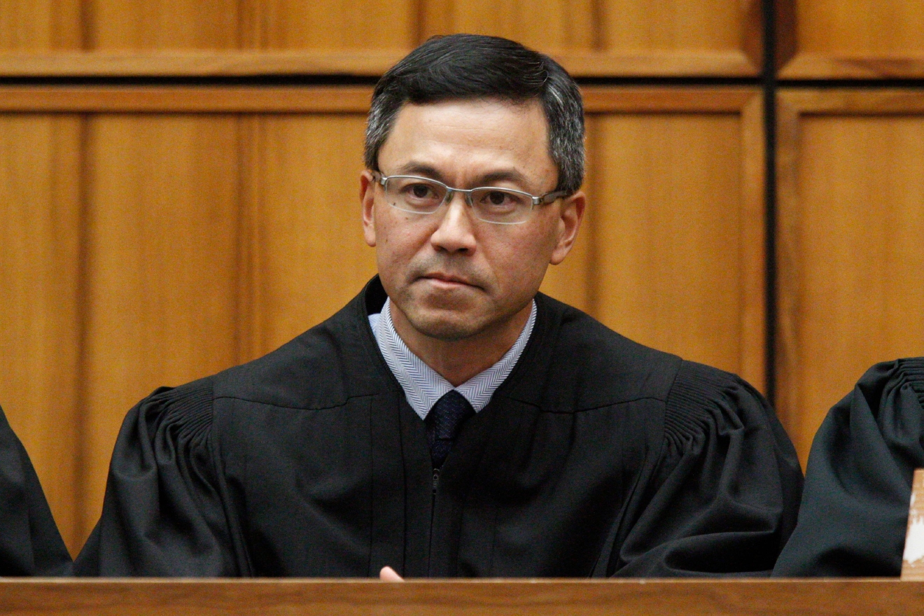 FILE  - This Dec. 2015 file photo shows U.S. District Judge Derrick Watson in Honolulu. Watson is hearing arguments Wednesday, March 29, 2017, in Honolulu, on whether to extend his temporary order blocking President Donald Trump's revised travel ban. But even if Watson doesn't put the ban on hold until the state's lawsuit is resolved, his temporary block would remain until he rules otherwise.  (George Lee/The Star-Advertiser via AP, File)