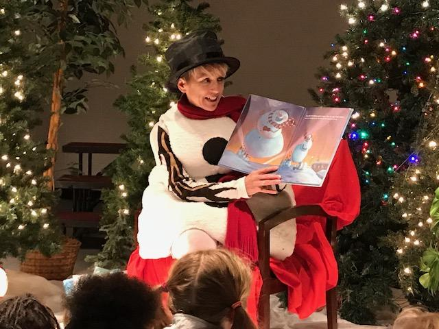 "Cynthia Sellinger read from the book ""What Snowmen Do at Night."" Fifth-graders and their first-grade buddies enjoyed cookies and hot chocolate as they listened and read along with the story. (Photo credit: WLOS staff)"