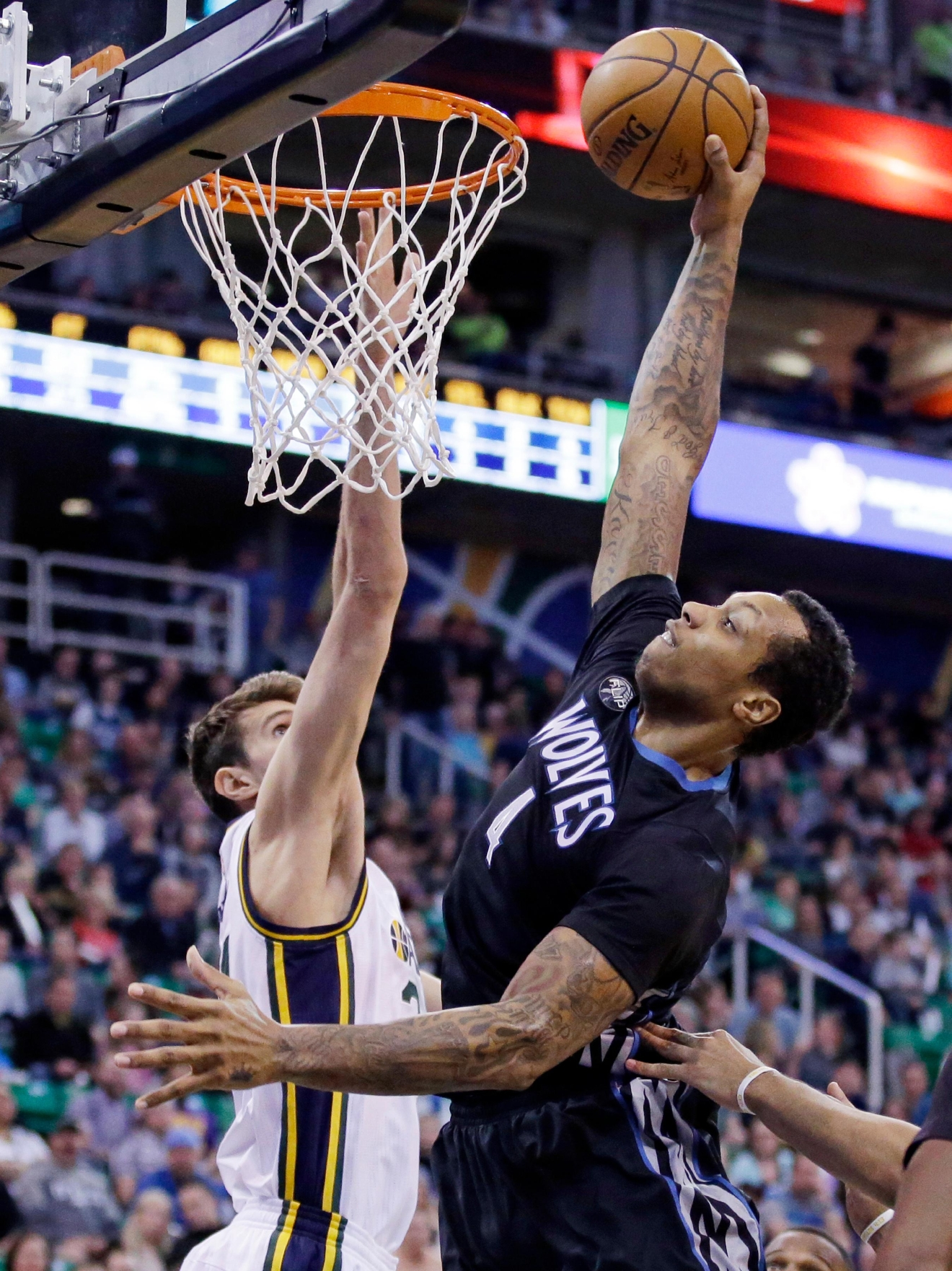 Minnesota Timberwolves forward Greg Smith (4) dunks the ball on Utah Jazz center Jeff Withey, left, during the second quarter of an NBA basketball game Friday, April 1, 2016, in Salt Lake City. (AP Photo/Rick Bowmer)