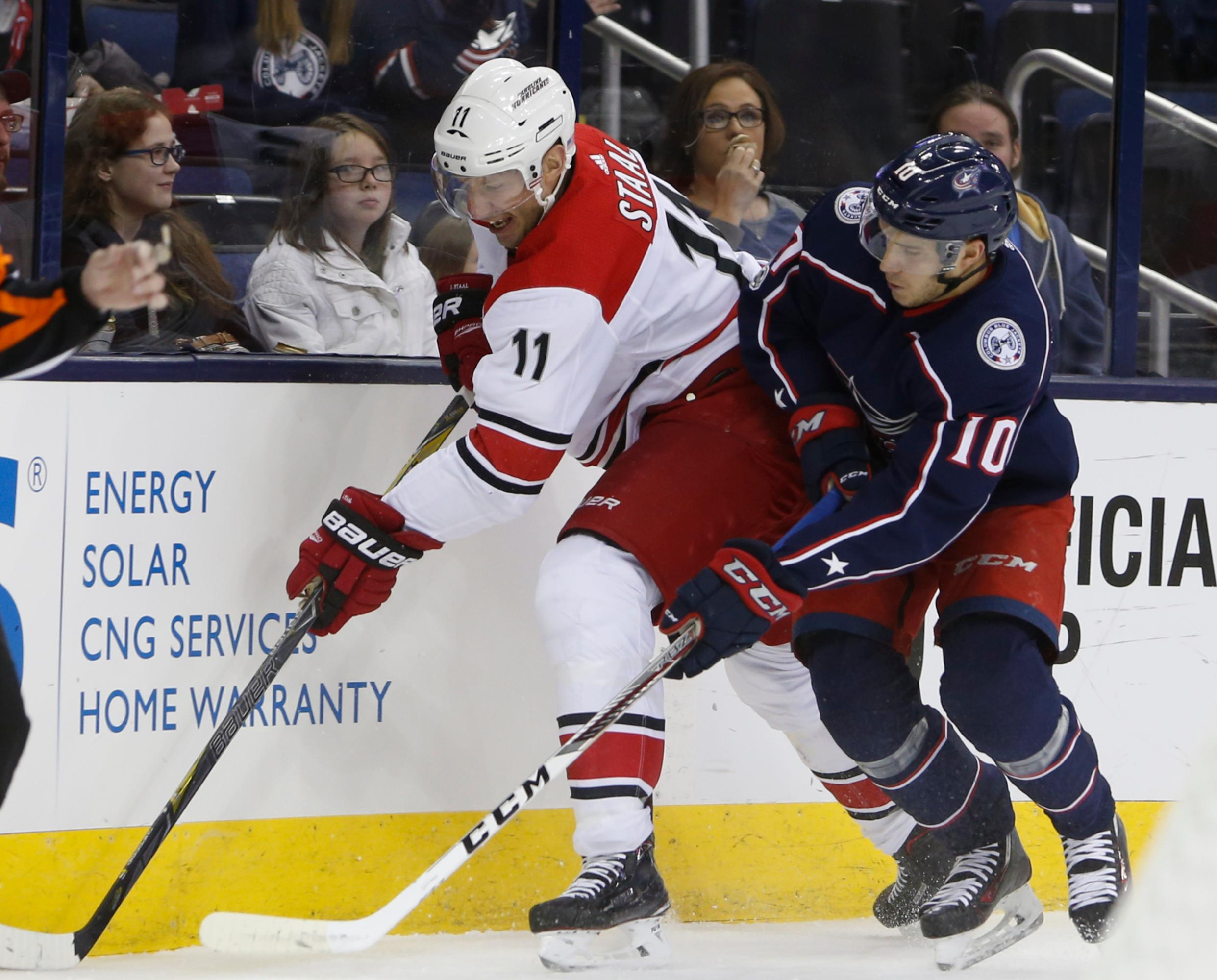 Carolina Hurricanes' Jordan Staal, left, and Columbus Blue Jackets' Alexander Wennberg, of Sweden, reach for the puck during the first period of an NHL hockey game Friday, Nov. 10, 2017, in Columbus, Ohio. (AP Photo/Jay LaPrete)