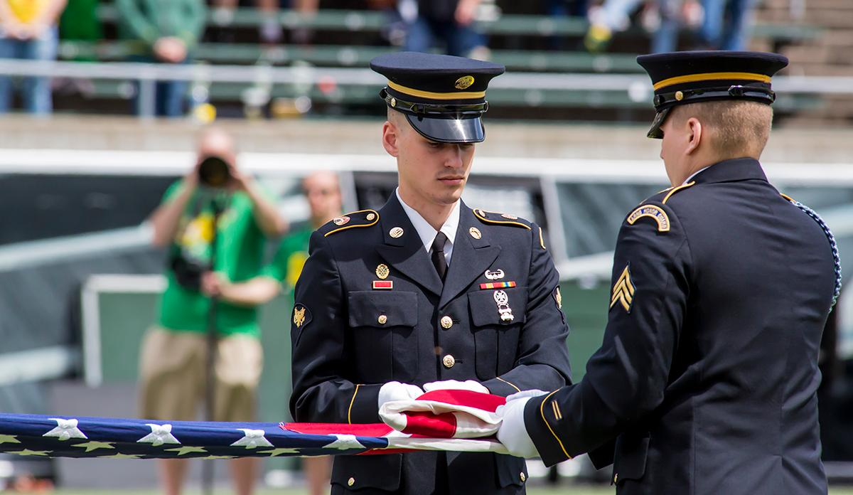Members of the United States Military fold a flag to present to the new Oregon Ducks head coach, Willie Taggart. The 2017 Oregon Ducks Spring Game provided fans their first glimpse at the team under new Head Coach Willie Taggart's direction. Team Free defeated Team Brave 34-11 on a sunny dat at Autzen Stadium in Eugene, Oregon. Photo by Ben Lonergan, Oregon News Lab