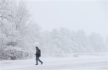 A motorist walks back to his car after helping a motorist stuck in a snow drift, Sunday, Jan. 5, 2014, in Zionsville, Ind.