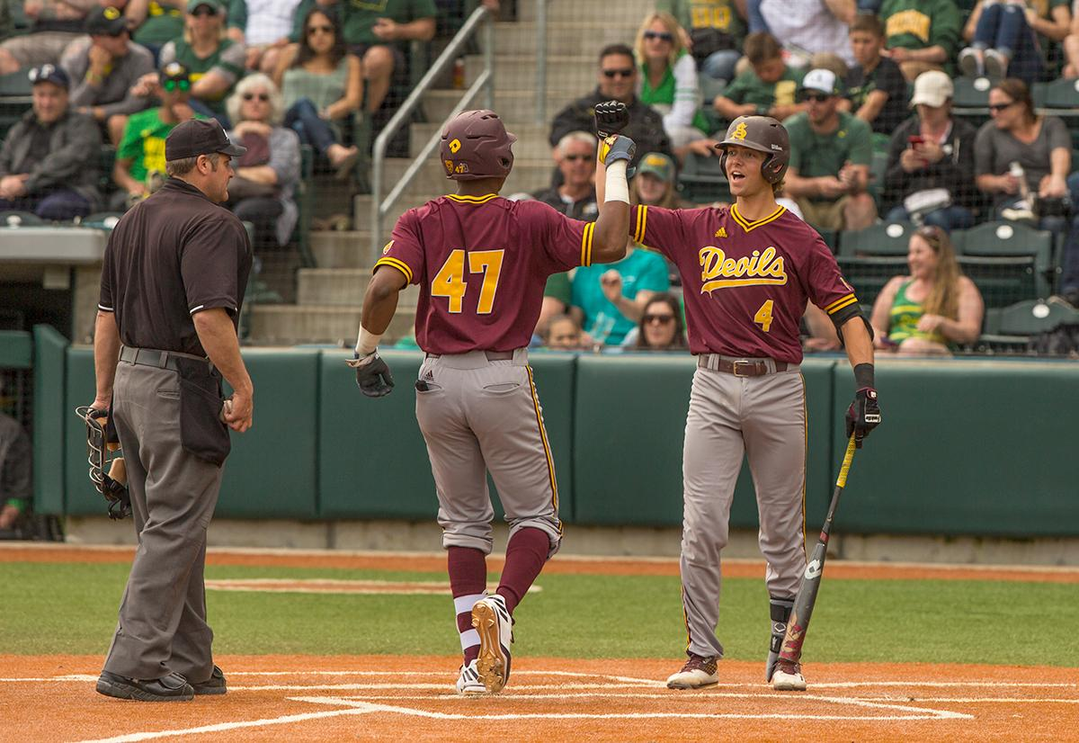 Andrew Snow(#4) gives a fist bump to Taylor Lane(#47) as he scores a run for the Sun Devils. Despite a late comeback, the Ducks fall to Arizona State Sun Devils 4-3 in the second game of a three-game series. Photo by James Wegter, Oregon News Lab