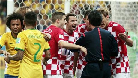 Croatia players argue with referee Yuichi Nishimura from Japan after being given a penalty during the group A World Cup soccer match between Brazil and Croatia, the opening game of the tournament, in the Itaquerao Stadium in Sao Paulo, Brazill.