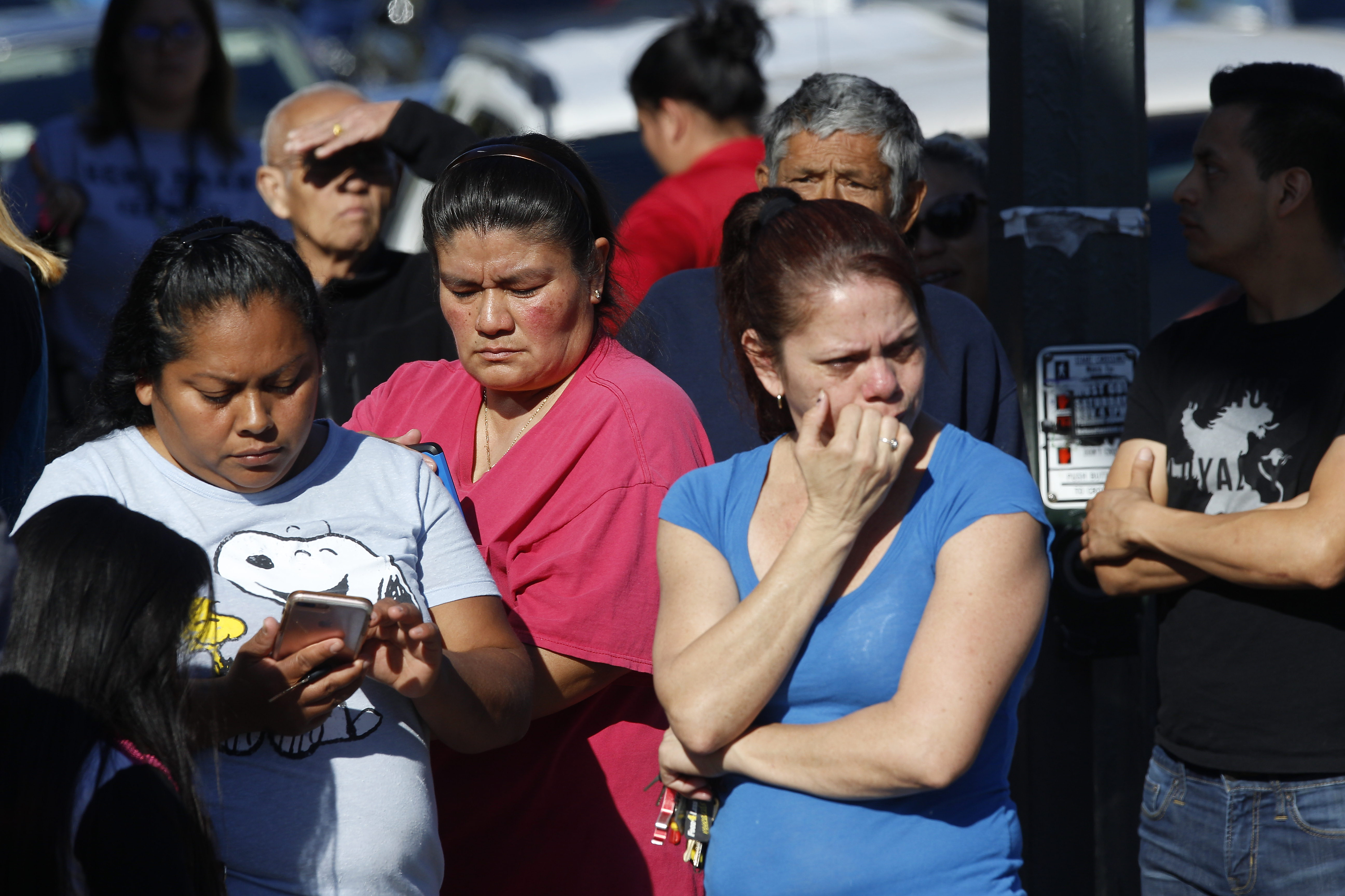 Parents wait for news of students at the Belmont High School in Los Angeles Thursday, Feb. 1, 2018. Two students were shot and wounded, one critically, inside a Los Angeles middle school classroom Thursday morning and police arrested a female student suspect, authorities said. (Damian Dovarganes)