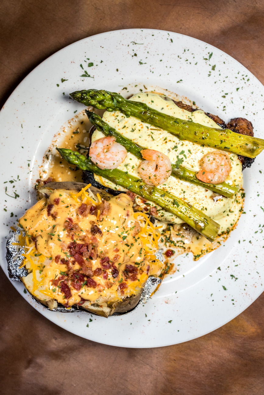 Oscar Rib-Eye: hand-cut and topped with shrimp, asparagus, and Bearnaise sauce served with a loaded baked potato / Image: Catherine Viox{ }// Published: 8.10.20