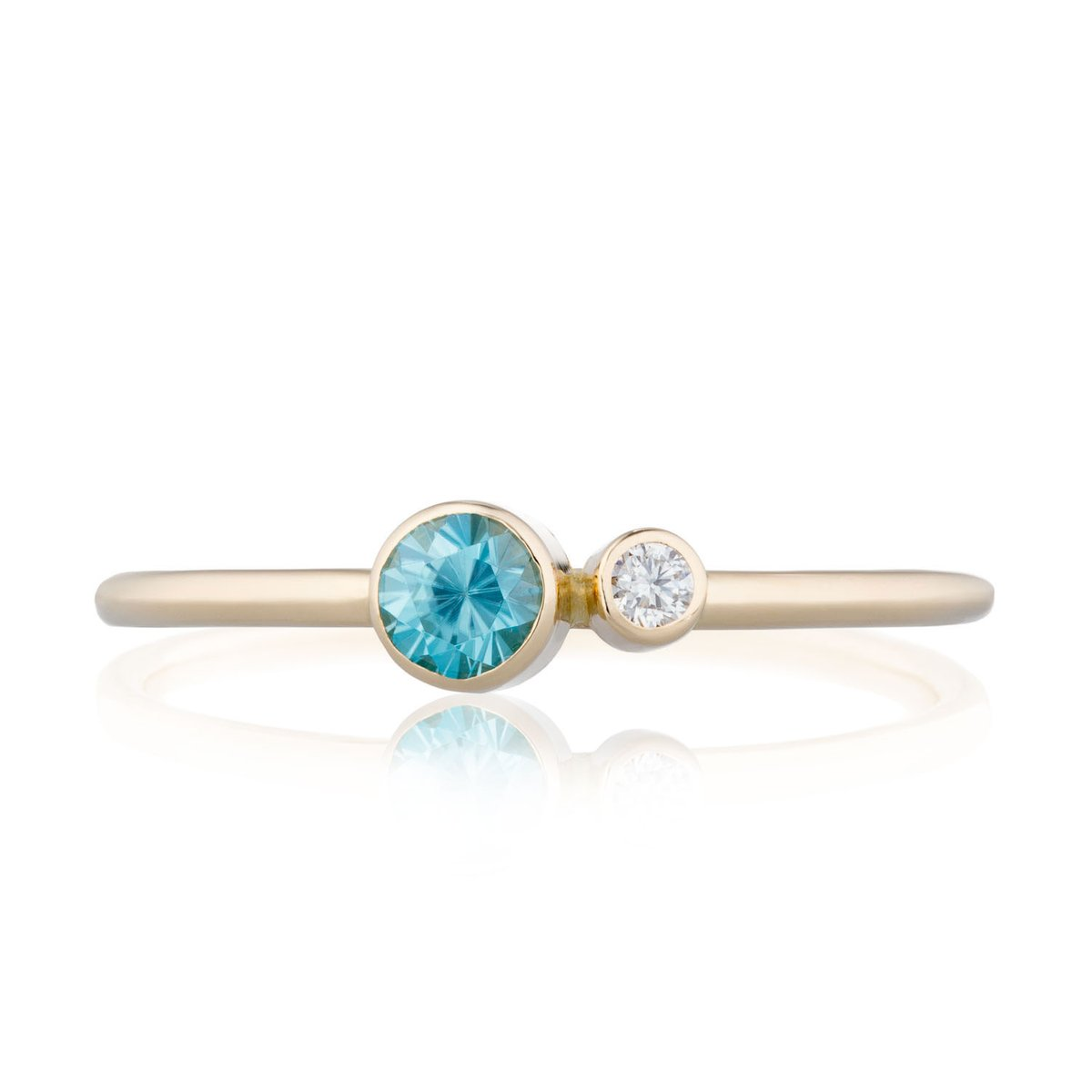 The sophisticated and stackable Blue Zircon Diamond Kiss Ring pairs a blue zircon with a dainty diamond. Made with a conflict-free Canadian diamond and SCS certified recycled 14K gold.