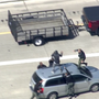 VIDEO: Murder suspect fleeing police runs onto freeway, leaps onto oncoming van