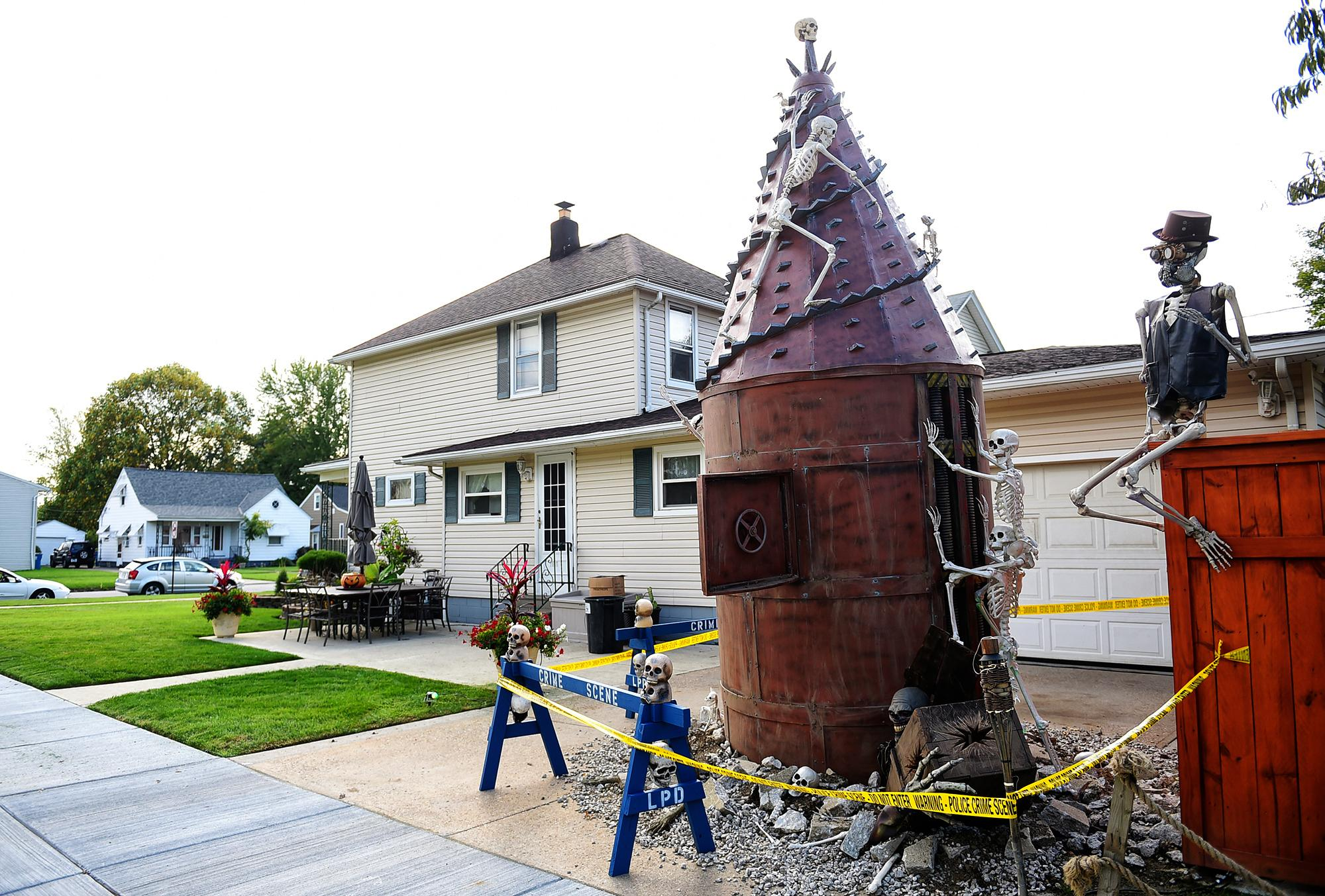 In an Oct.12, 2017 photo, Ricky and Marlene Rodriguez's home at the corner of 30th St. and Tacoma Ave., in Lorain, Ohio, has morphed from a pirate ship, to a train and now into a digging machine poking through the home's driveway. The home is an annual attraction for neighbors and passersby within the city.  (Kristin Bauer/Chronicle-Telegram via AP)