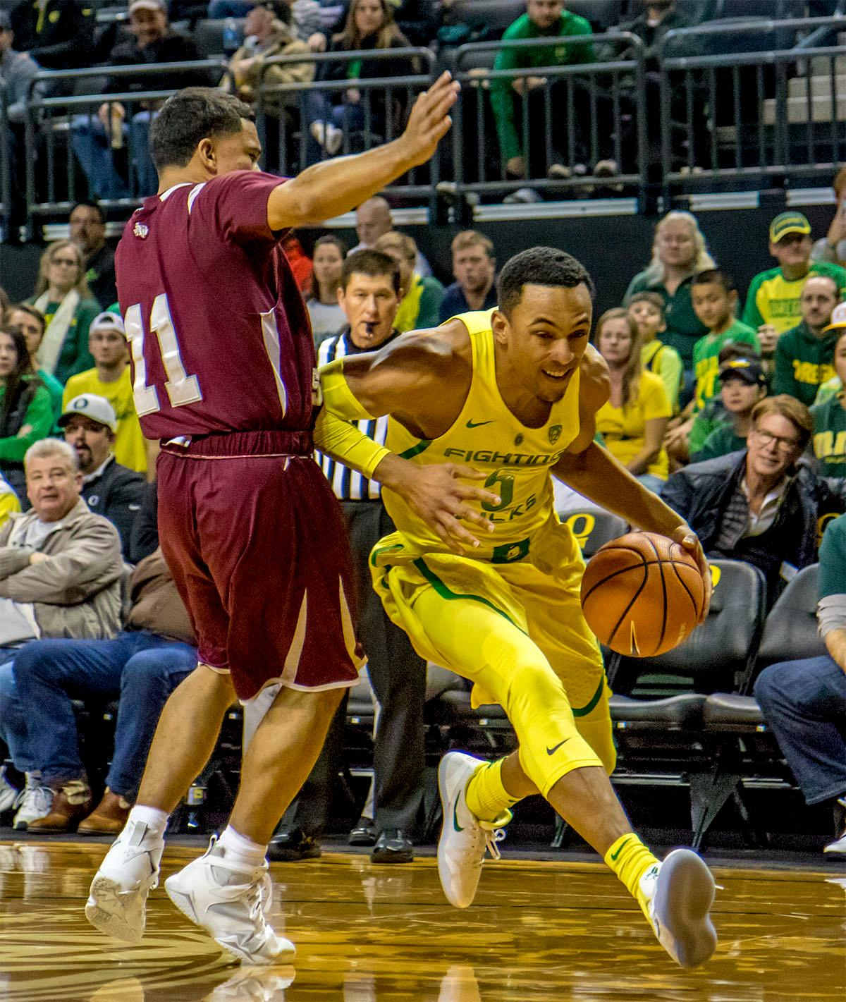 The Duck's Elijah Brown (#5) makes a run for the basket past the Tiger's Brian Carey (#11). The Oregon Ducks defeated Texas Southern Tigers 74-68. The Ducks are now 7-3 overall in the Pac-12. Photo by August Frank. Oregon News Lab