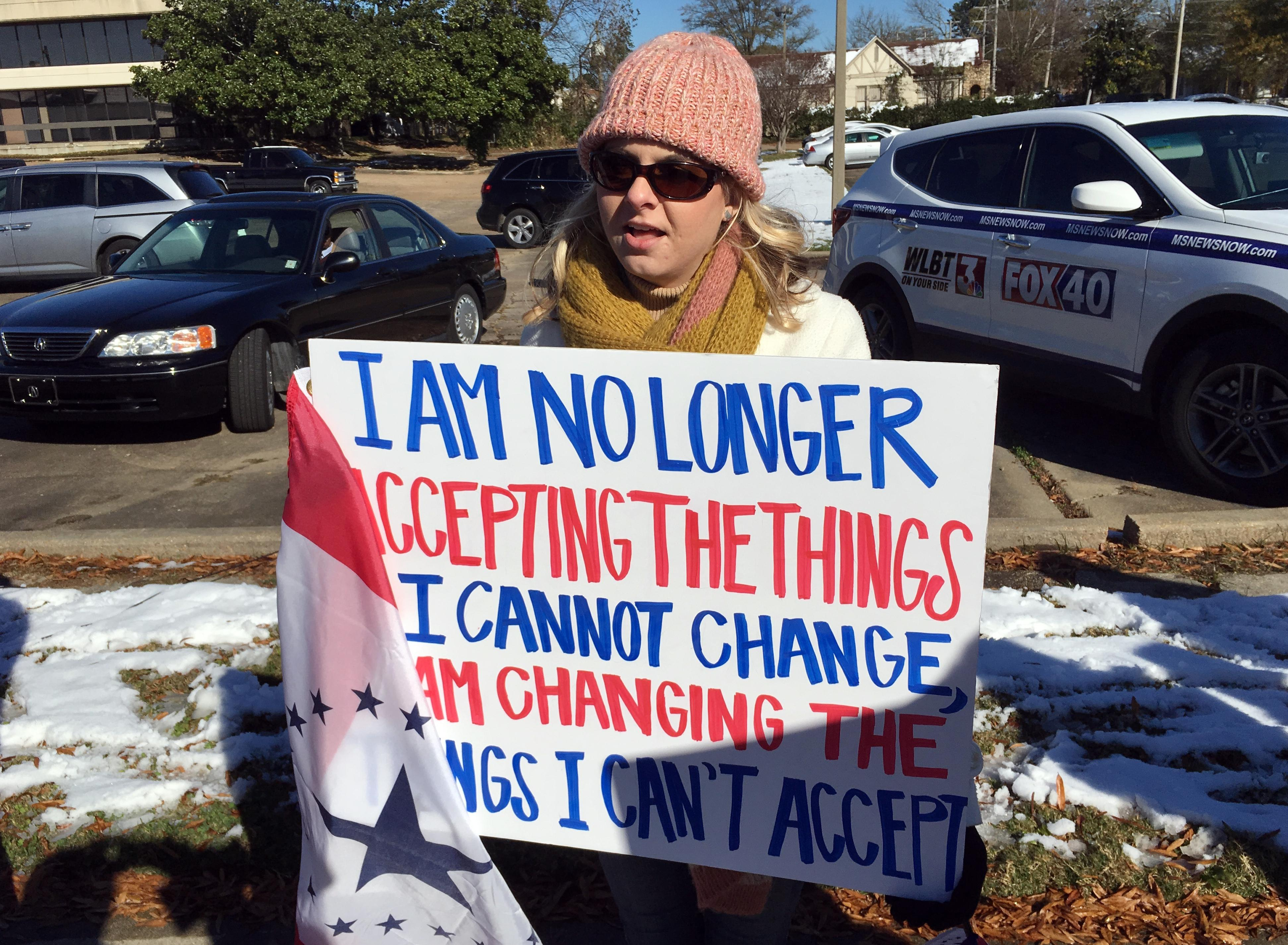 Keller White of Jackson, Miss., protests Saturday, Dec. 9, 2017, against the visit of President Donald Trump in Jackson, Miss. (AP Photo/Jeff Amy)