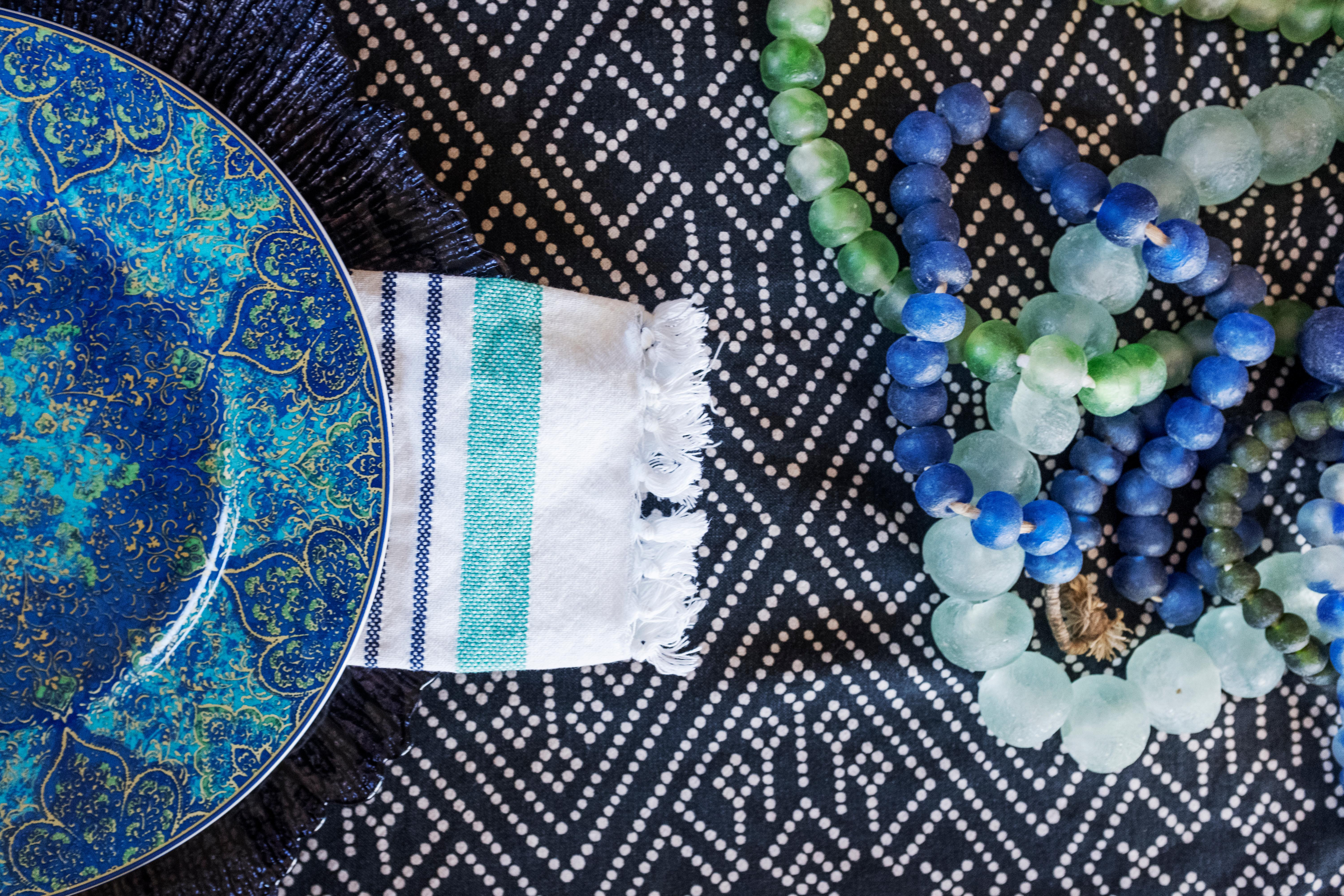 Source your closet. Add colorful beaded necklaces to the center of the table, or grab some colorful bracelets to wrap around a votive candle holder. Bracelets also make great napkin rings. Unexpected textural elements add interest and depth to your table. (Image: Ashley Hafstead)