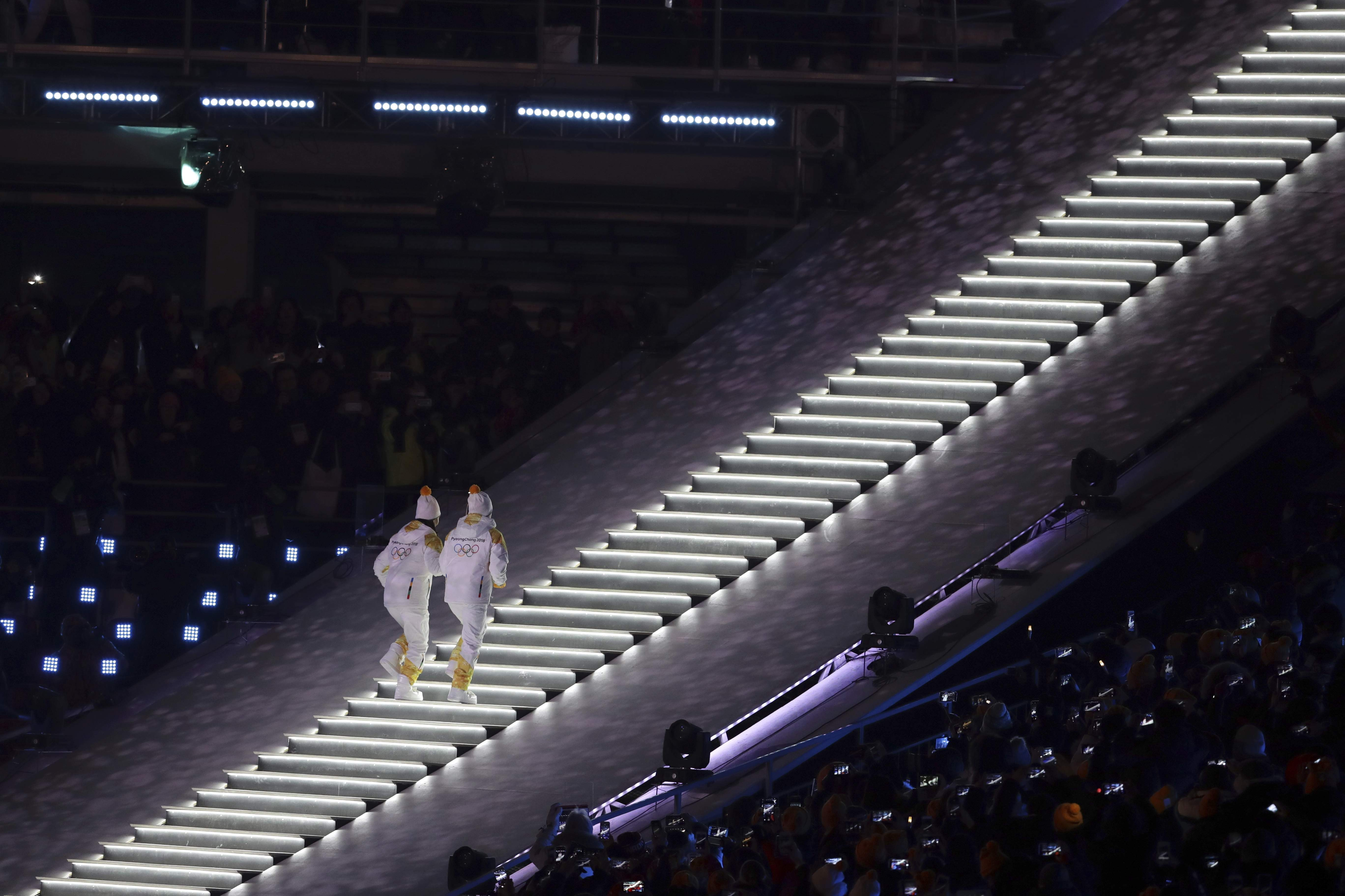 North Korea's Jong Su Hyon and South Korea's Park Jong-ah carry the Olympic torch is carried during the opening ceremony of the 2018 Winter Olympics in Pyeongchang, South Korea, Friday, Feb. 9, 2018. (AP Photo/Michael Sohn)