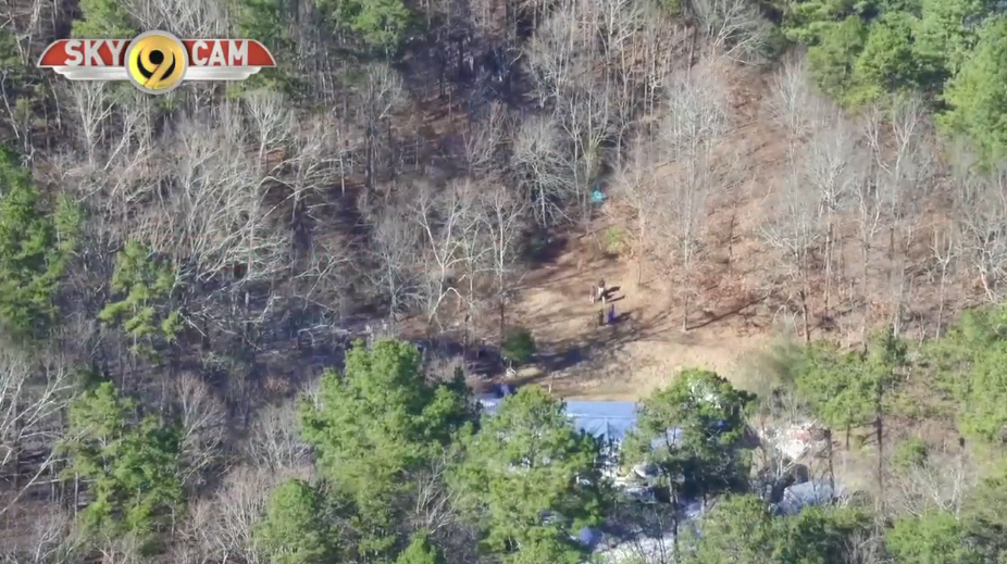 Footage from the NewsChannel 9 SkyCam shows a green tarp stretched out in the woods as search efforts continue in the surrounding area.