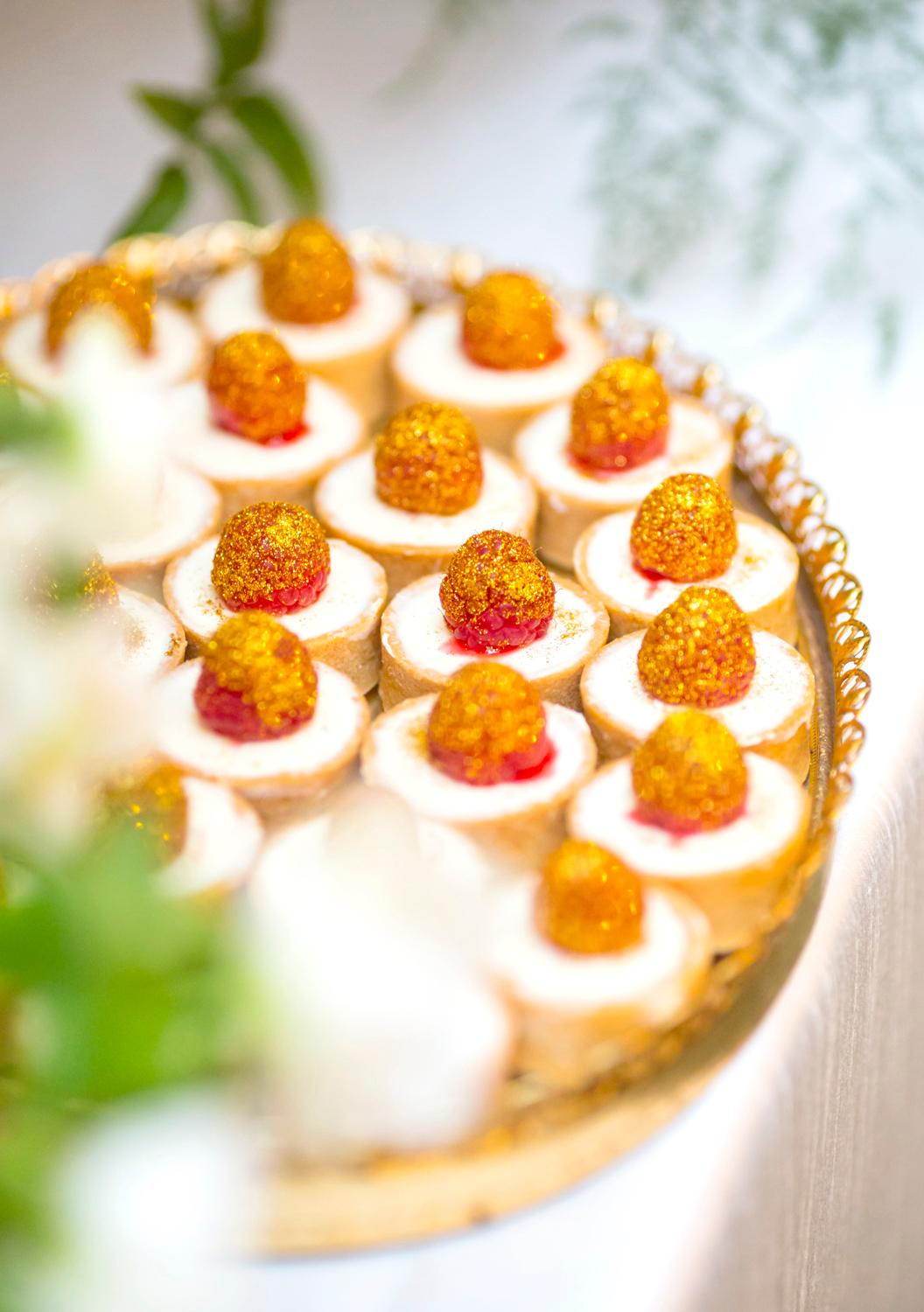 Golden Raspberry Topped Tart Bites are on display by Trophy Cupcakes for the VIP Wedding Tasting at their bakery at the Bravern. Guests of the VIP Wedding Tasting got to try the delectable cupcakes, 6-inch cakes, macarons, meringues, and other goodies on display while sipping champagne. (Sy Bean / Seattle Refined)<p></p>