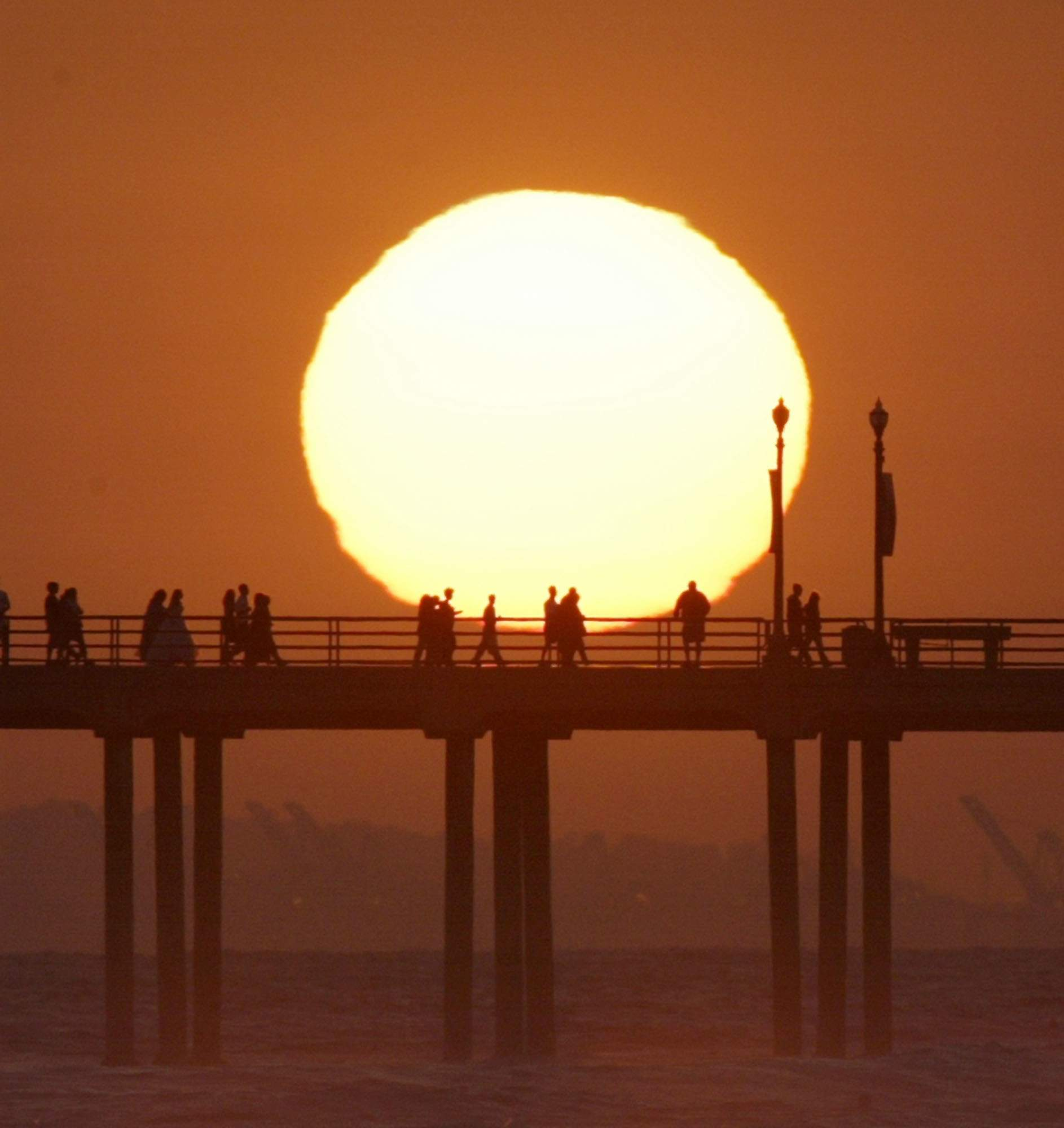 In this Saturday, May 29, 2004, file photo, people gather on a pier in Huntington Beach, Calif., as the sun sets. NICK UT/THE ASSOCIATED PRESS