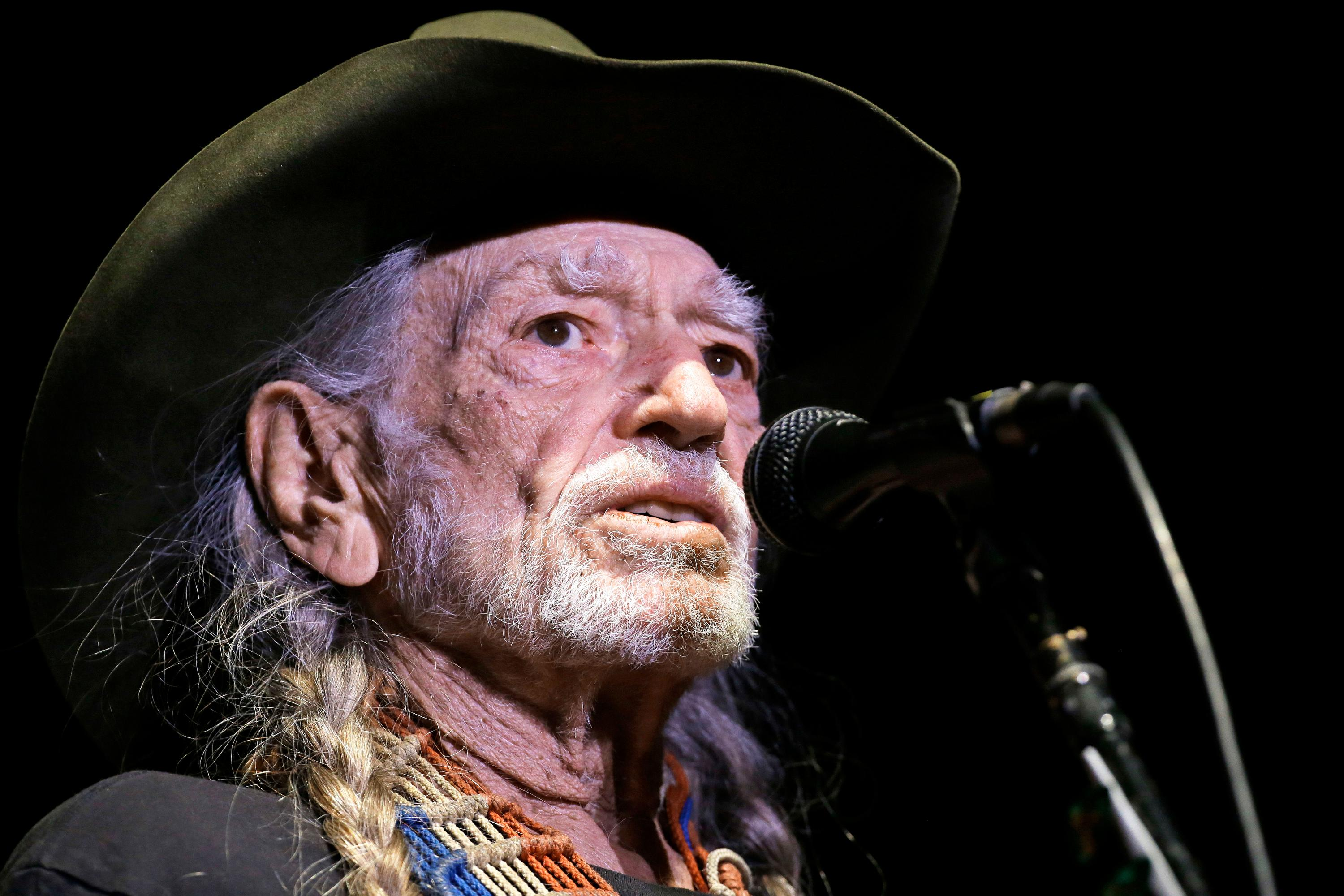 "FILE - In this Jan. 7, 2017, file photo, Willie Nelson performs in Nashville, Tenn. Nelson has called out current immigration policies as ""outrageous"" and extended an offer to meet President Donald Trump at one of the detention centers at the U.S.-Mexico border. (AP Photo/Mark Humphrey, File)"
