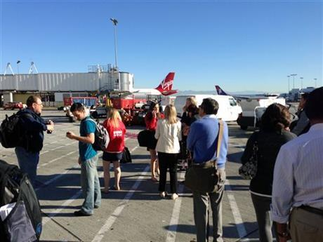In this photo provided by John Forstrom, which has been authenticated based on its contents and other AP reporting, people wait on the tarmac at Los Angeles International Airport, Friday.