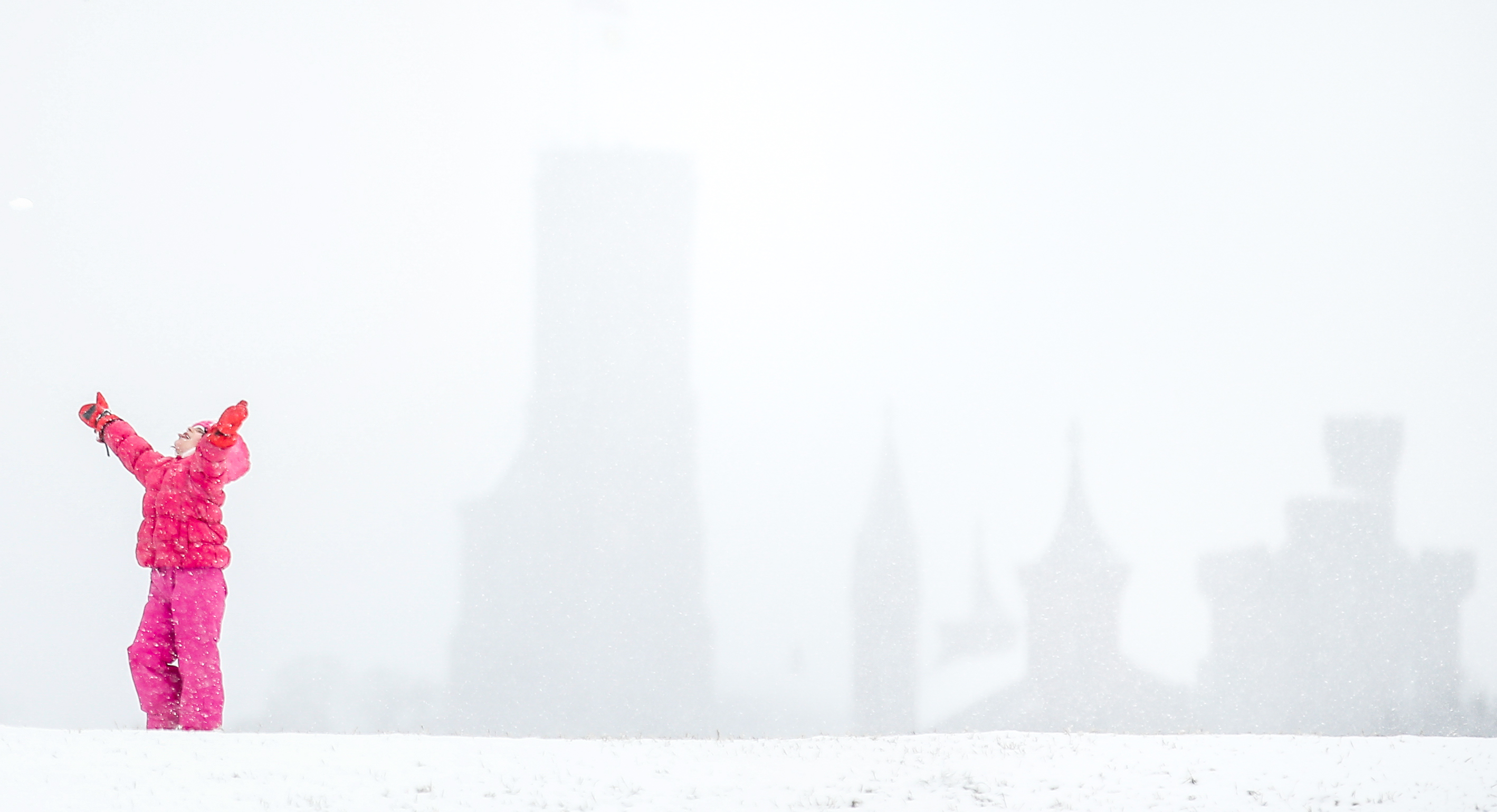 The Smithsonian Institution Building, known as The Castle, is visible behind Mia Molnar, 6, of Tampa, Fla., who plays in the snow on the National Mall in Washington, Thursday, March 5, 2015. The U.S. federal government said its offices in the Washington area will be closed Thursday because of a new round of winter weather expected in the region. The Office of Personnel Management said non-emergency personnel in and around Washington were granted excused absences for the day. Emergency employees and telework-ready employees were expected to work. (AP Photo/Andrew Harnik)
