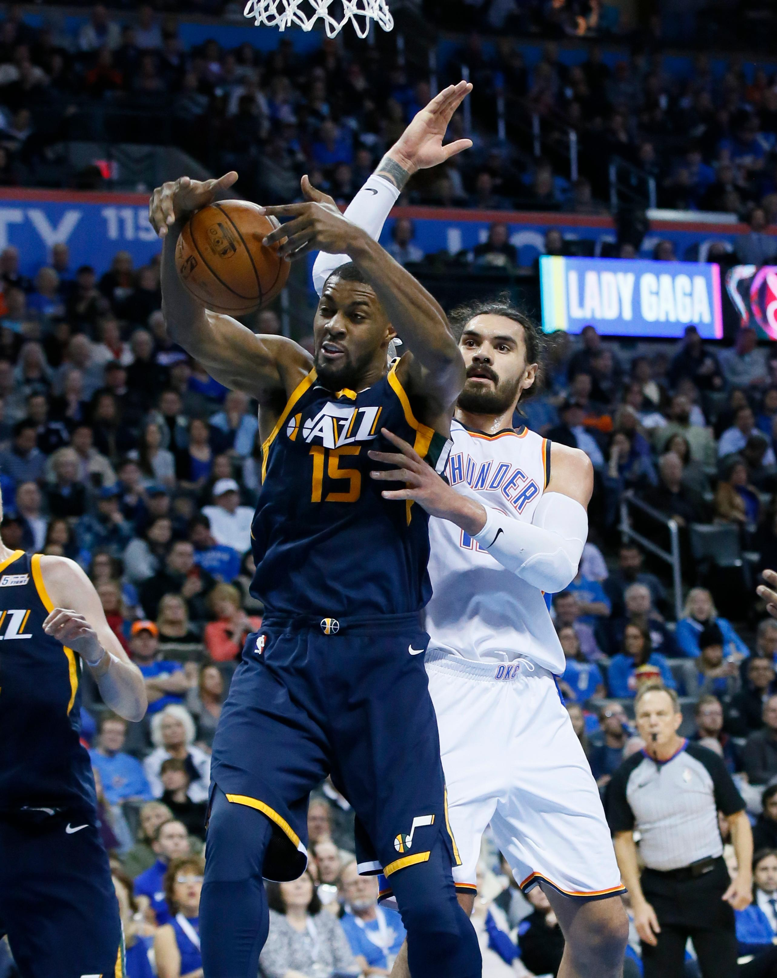 Utah Jazz forward Derrick Favors (15) grabs a rebound in front of Oklahoma City Thunder center Steven Adams, right, in the second quarter of an NBA basketball game in Oklahoma City, Tuesday, Dec. 5, 2017. (AP Photo/Sue Ogrocki)