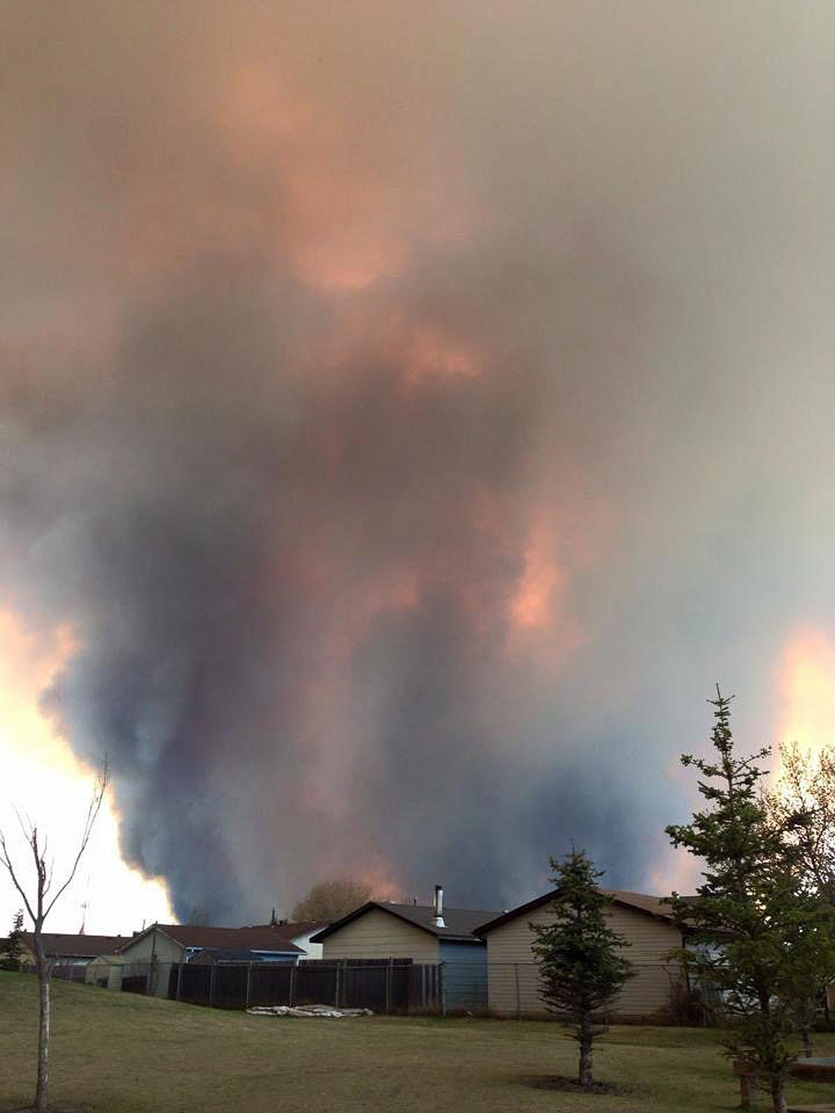 Fire burns and smoke fills the air near homes in Fort McMurray, Alberta, on Tuesday May 3, 2016. The entire population of the Canadian oil sands city of Fort McMurray, has been ordered to evacuate as a wildfire whipped by winds engulfed homes and sent ash raining down on residents.  (Kitty Cochrane/The Canadian Press via AP) MANDATORY CREDIT