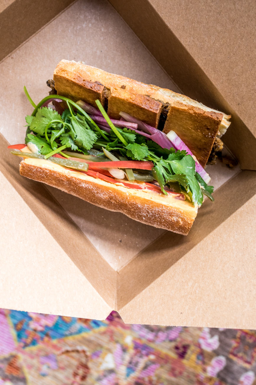 "Vegan Banh Mi: sliced and fried tofu, mushroom and black bean pate, spicy ""mayo"", pickles, radishes, and cilantro on a baguette / Image: Catherine Viox{ }// Published: 6.23.20"