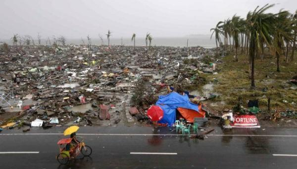 People ride past destruction in the coastal city of Tacloban. Many badly hit cities and islands were cut off, making it difficult to estimate the number of casualties early on.