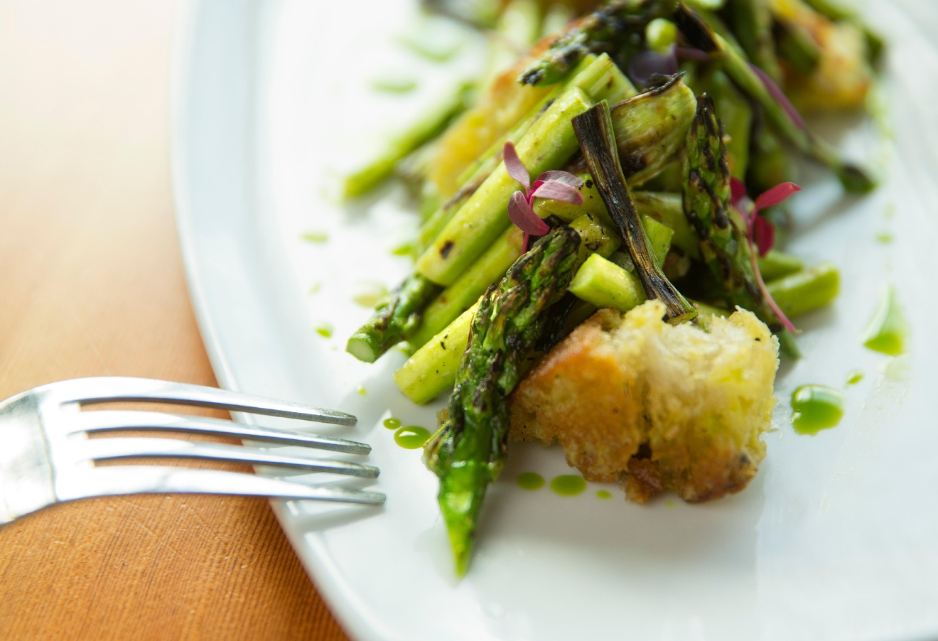 Fresh asparagus, crouton, and charred ramp vinaigrette, prepared by Chef Addam Buzzalini at Tavoláta Capitol Hill. (Sy Bean / Seattle Refined)