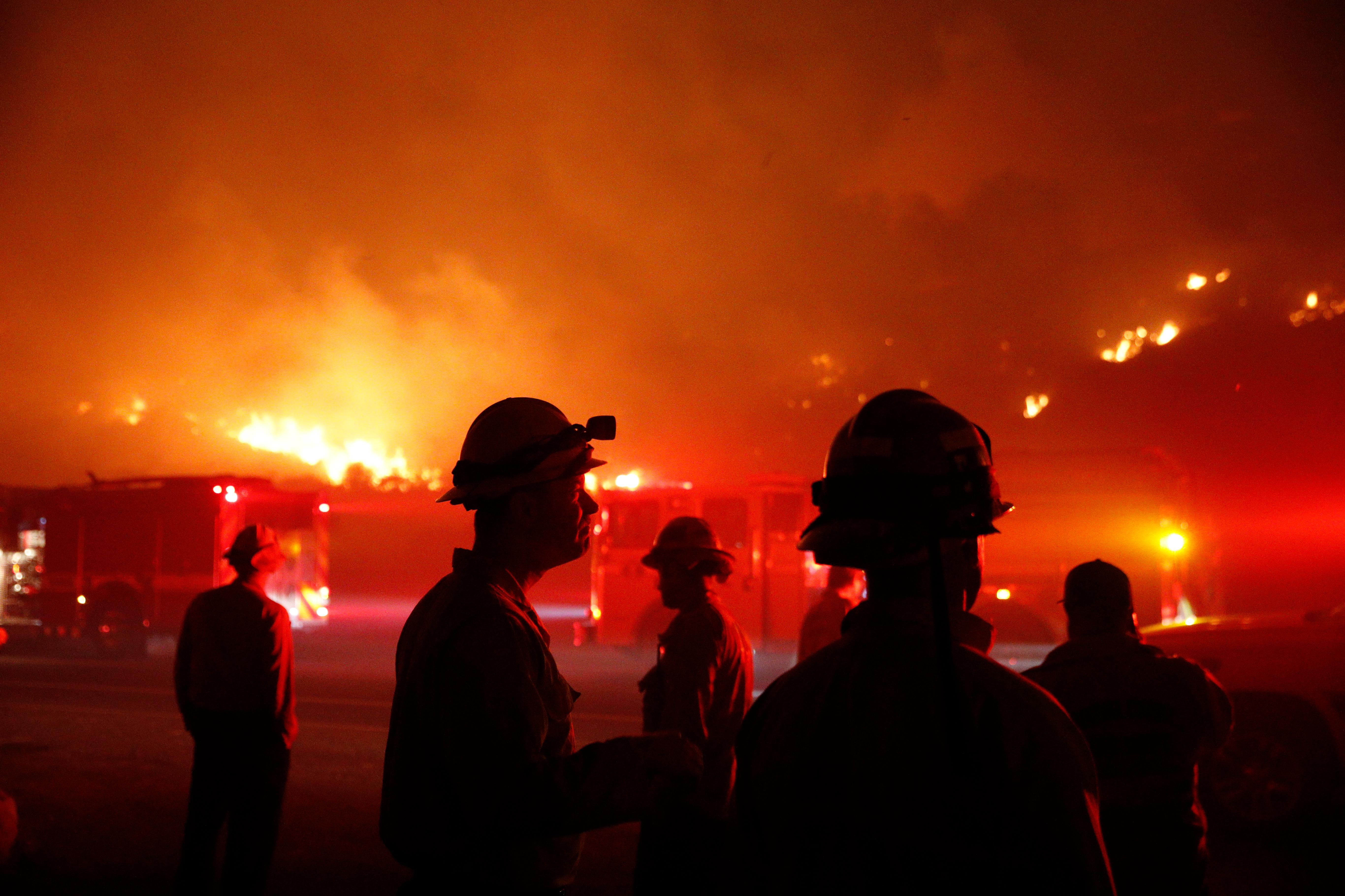 Firefighters gather in front of a residential area as a wildfire burns along the 101 Freeway Tuesday, Dec. 5, 2017, in Ventura, Calif. Raked by ferocious Santa Ana winds, explosive wildfires northwest of Los Angeles and in the city's foothills burned a psychiatric hospital and scores of homes and other structures Tuesday and forced the evacuation of tens of thousands of people. (AP Photo/Jae C. Hong)