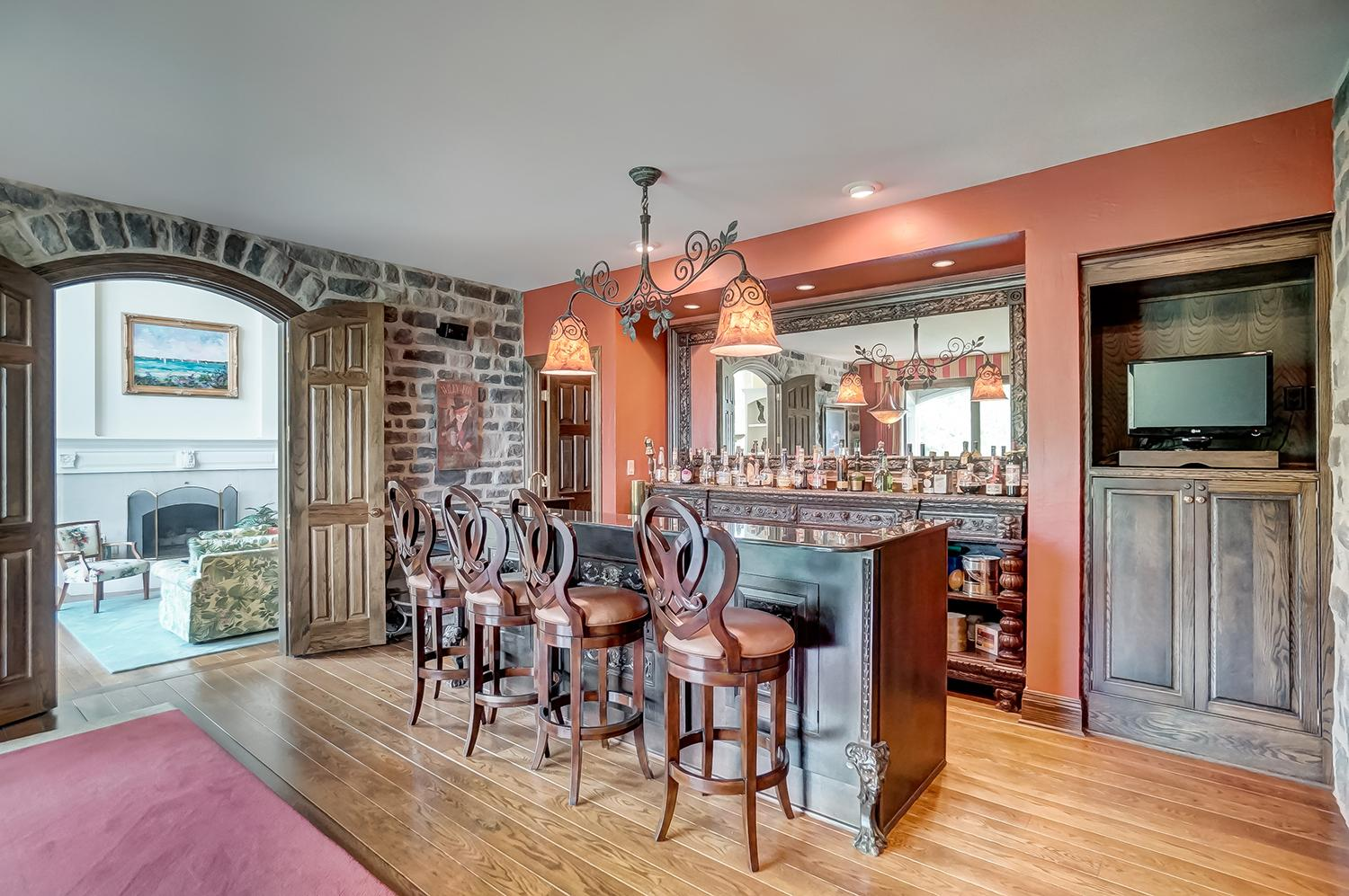 English-style pub room with charming, old stone walls, 100-year-old antique, hand-carved bar from England crowned with granite and seats four comfortably / Image: Wow Video Tours // Published: 6.8.18