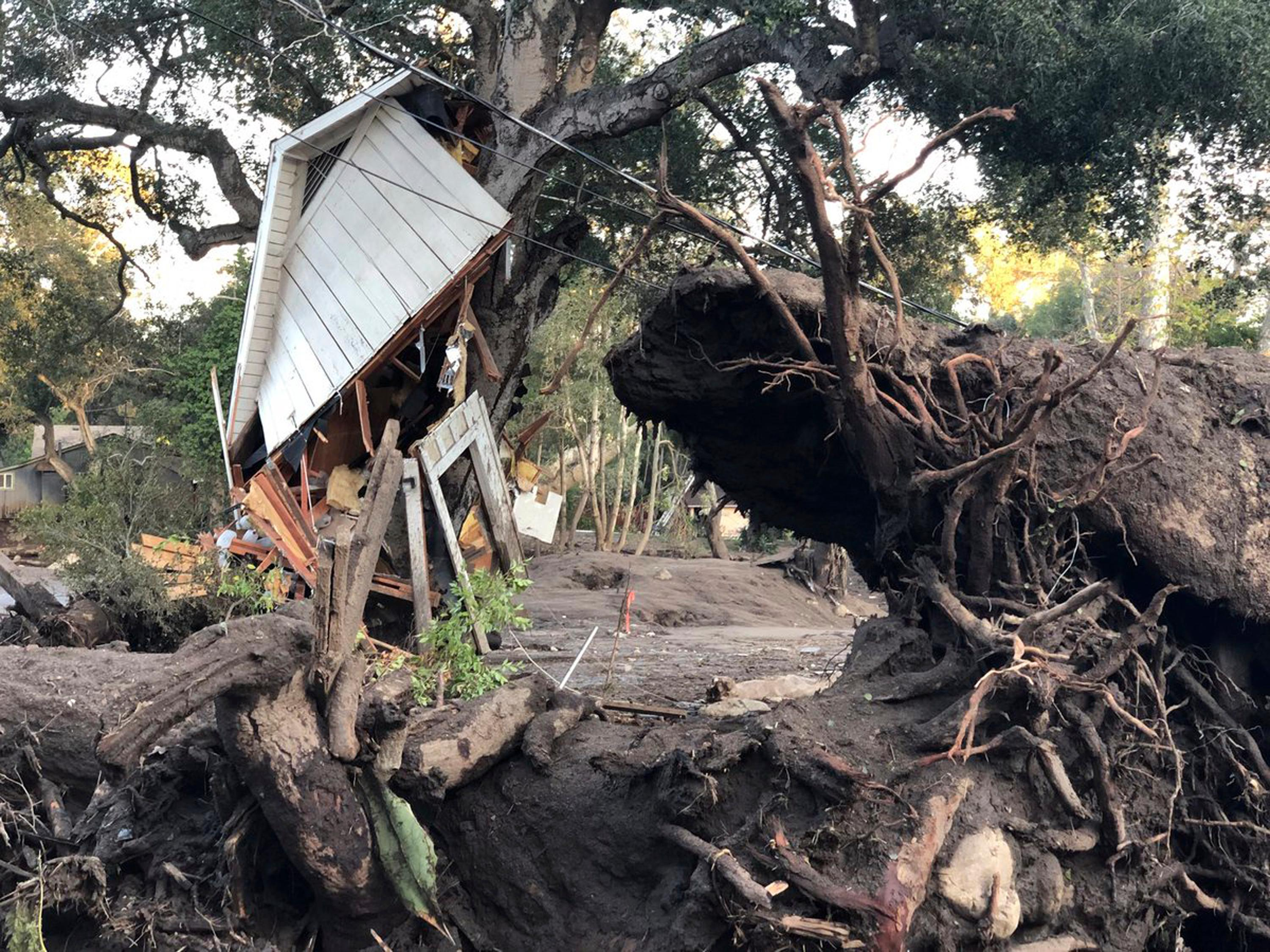 This photo provided by the Santa Barbara County Fire Department shows mud, boulders, and debris that destroyed homes that lined Montecito Creek near East Valley Road in Montecito, Calif., Wednesday, Jan. 10, 2018. Anxious family members awaited word on loved ones Wednesday as rescue crews searched grimy debris and ruins for more than a dozen people missing after mudslides in Southern California on Tuesday destroyed over a 100 houses, swept cars to the beach and left more than a dozen victims dead.  (Mike Eliason/Santa Barbara County Fire Department via AP)