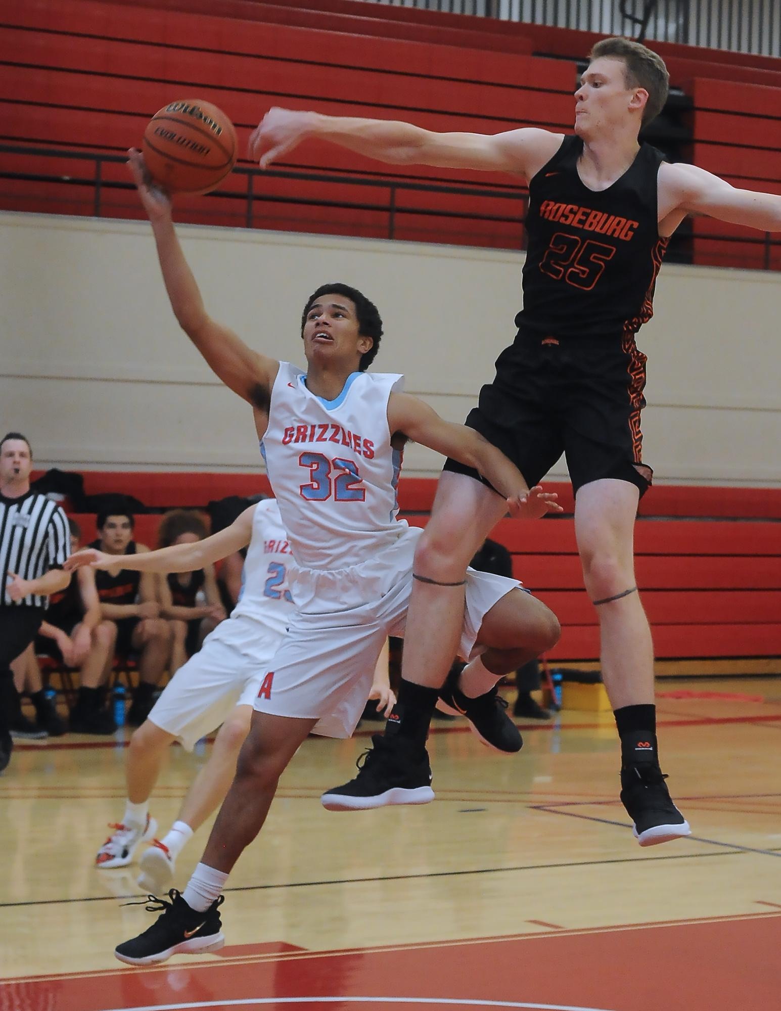 Johnathan Stone, (25), defends a shot by Austin Harris (32). Photo by Denise Baratta
