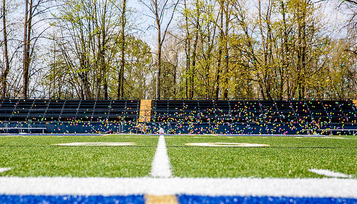 The eggs hit the field. Hundreds of kids from young babies to school age converged on Marist High School on Saturday for a helicopter Easter egg drop. The event, put on by Joy Church, loaded up a large bucket with eggs then dropped it across the Marist football field by helicopter. Photo by August Frank, Oregon News Lab