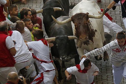 Revelers run with a Jandilla's ranch fighting bulls during the running of the bulls of the San Fermin festival in Pamplona, Spain, Tuesday.